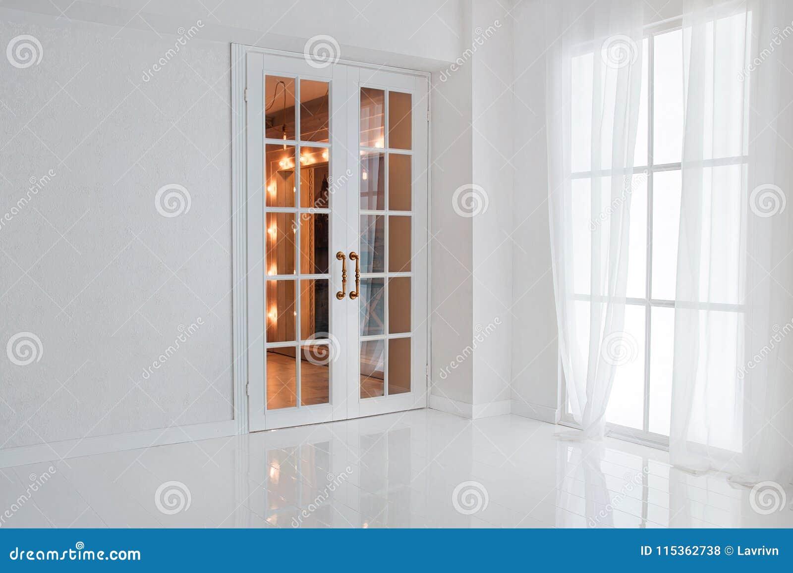 Esvazie a sala branca com janela grande e a porta francesa de vidro com luzes alaranjadas brilhantes