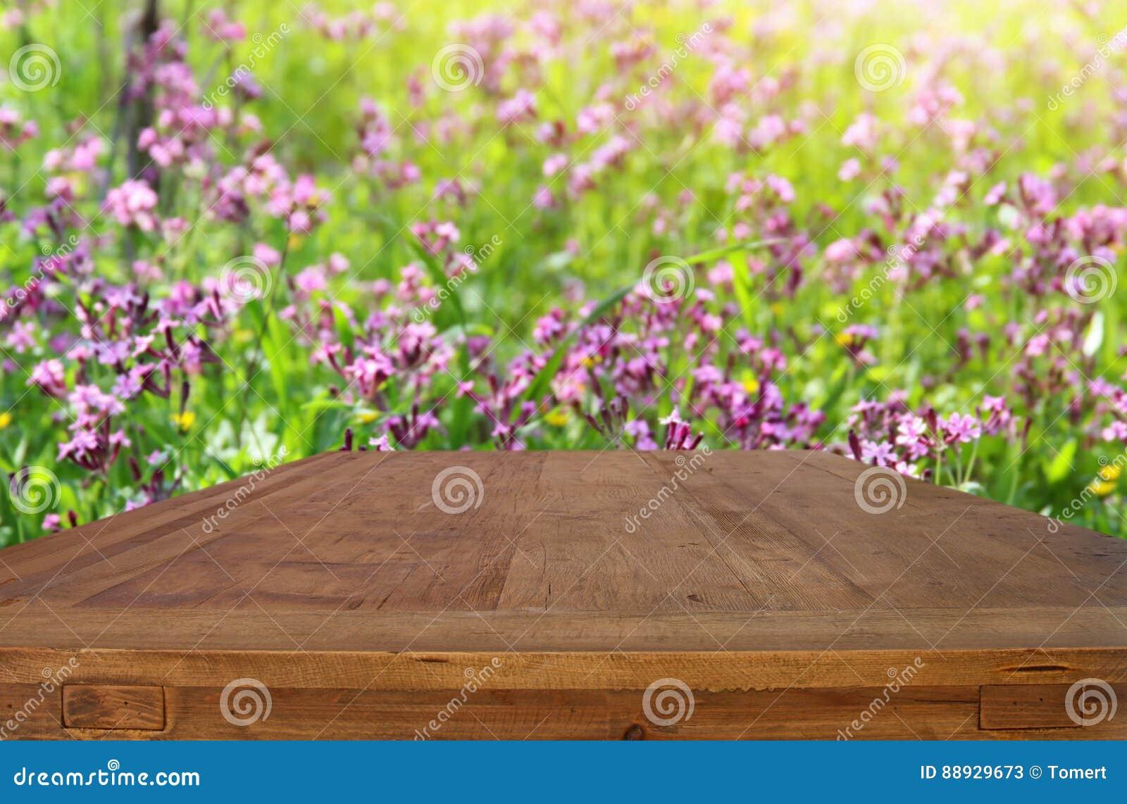 Esvazie a tabela rústica na frente do fundo bonito das flores da mola