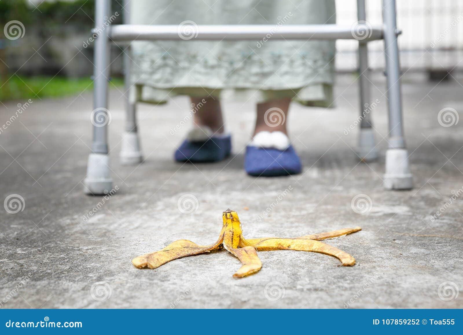 Etapa idosa descuidada da mulher sobre uma casca da banana