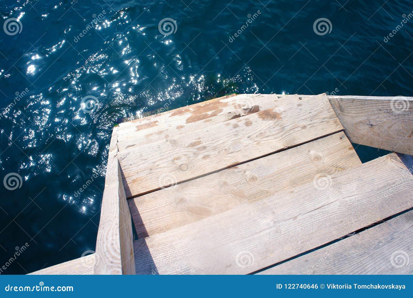 Etapas de madeira com os corrimão que conduzem à água com uma reflexão do céu