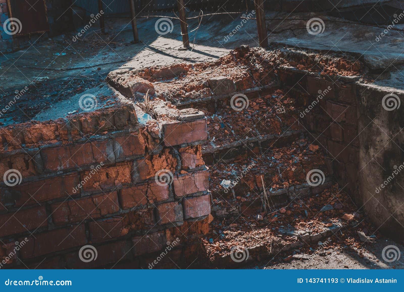 Etapas de pedra quebradas do tijolo parcialmente cobertos de vegetação com a grama