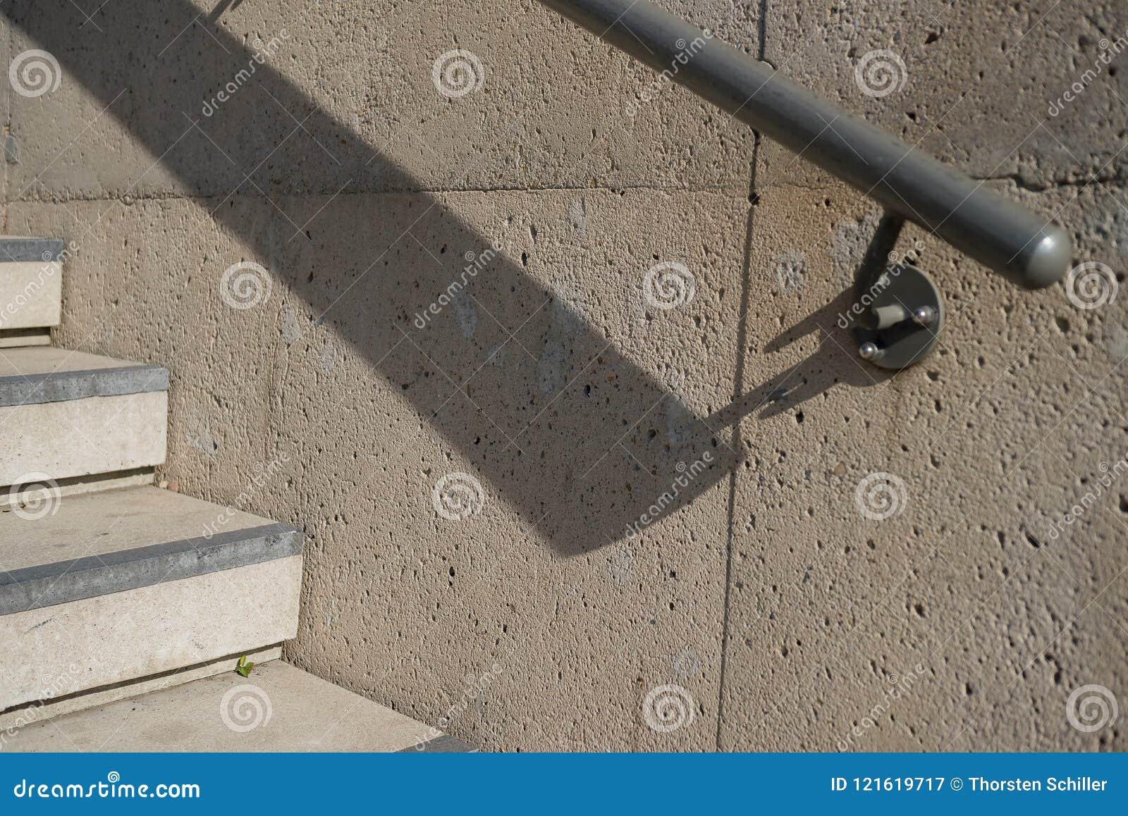 Etapas do corrimão e da escada do concreto com sombra profunda