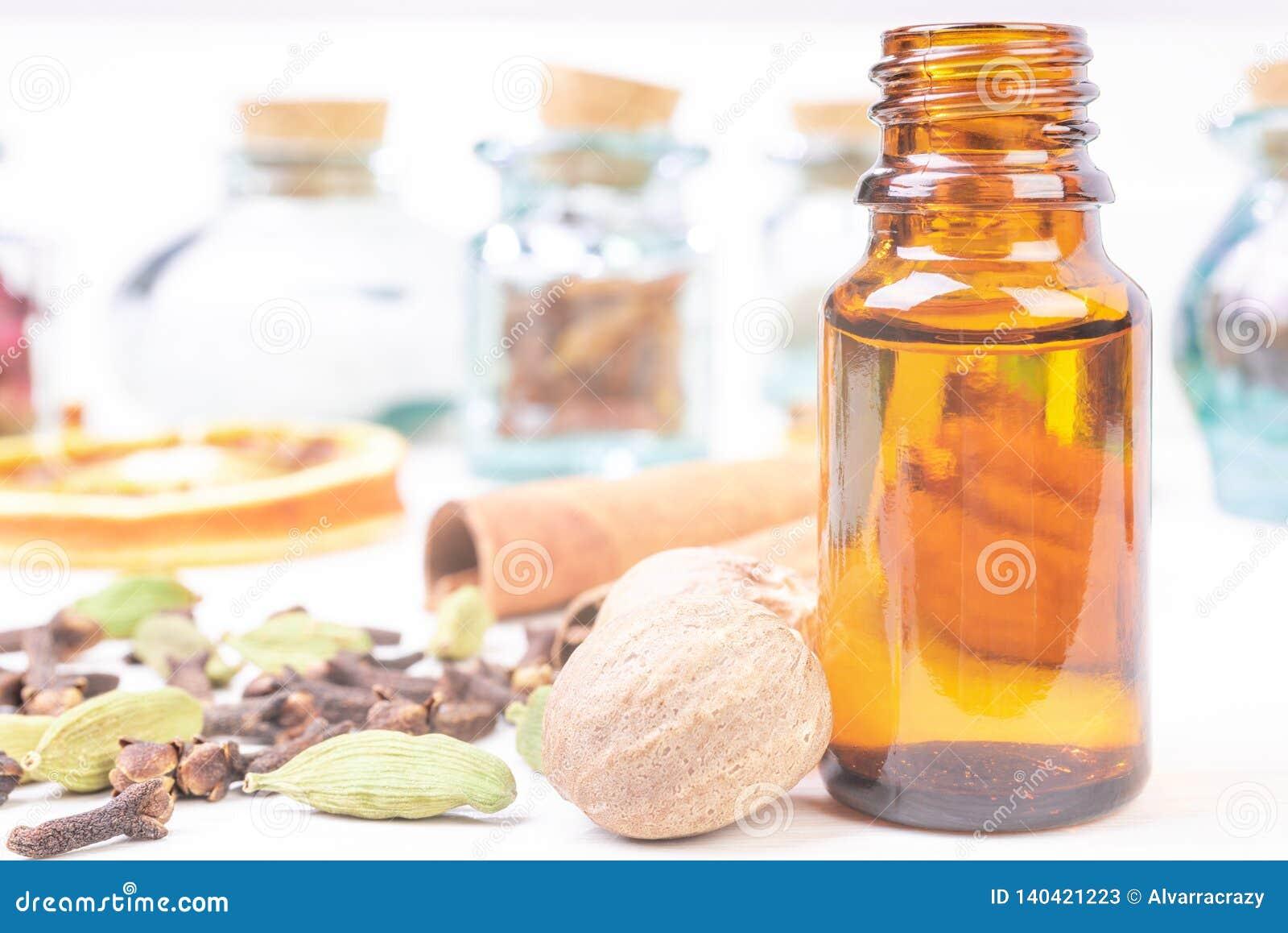 Etherische oliën in het meisje van glasflessen van kruiden en notemuskaat, cardamon, kaneel, kruidnagel op de houten achtergrond