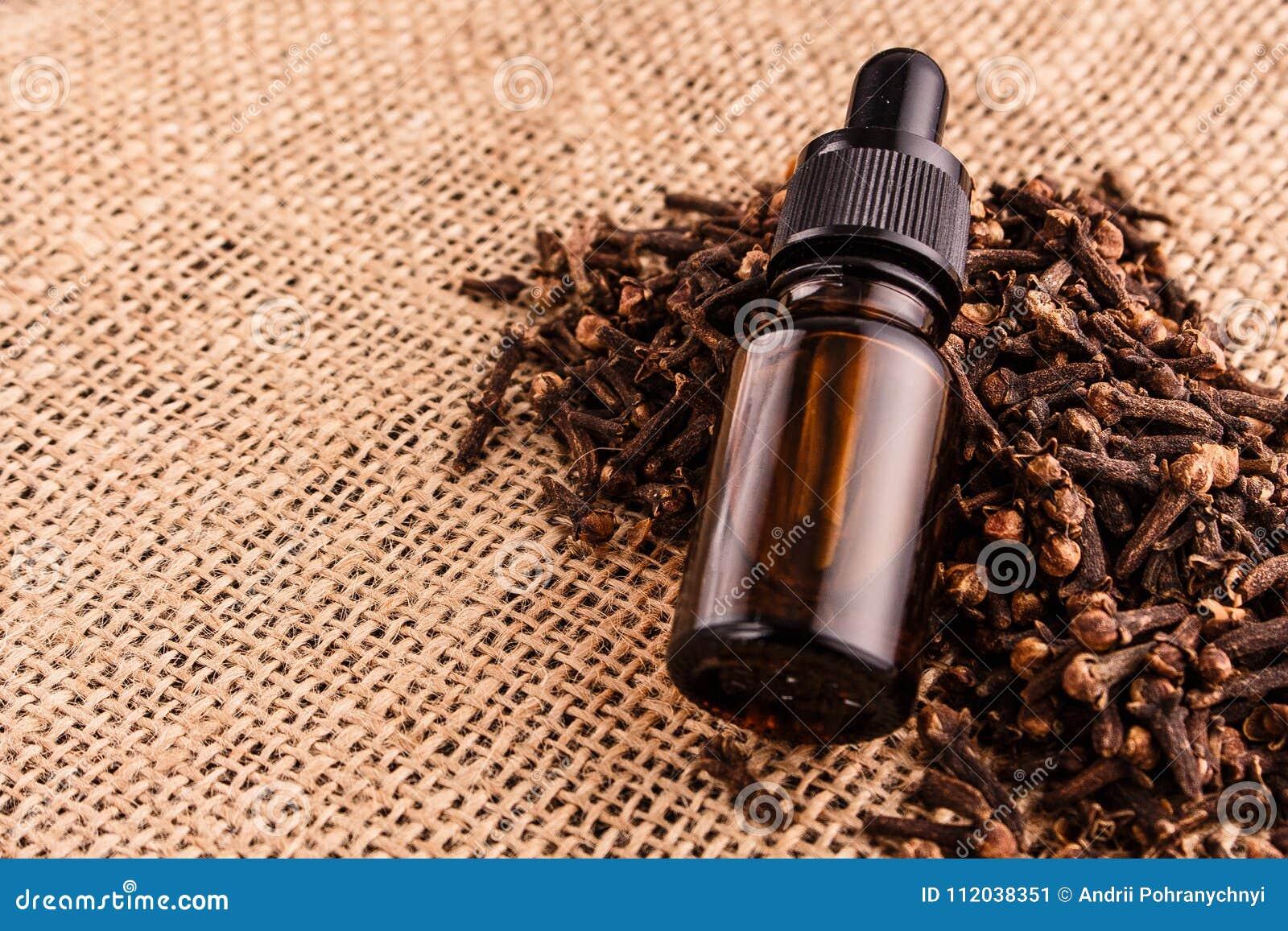 Etherische olie van kruidnagels op een houten rustieke achtergrond