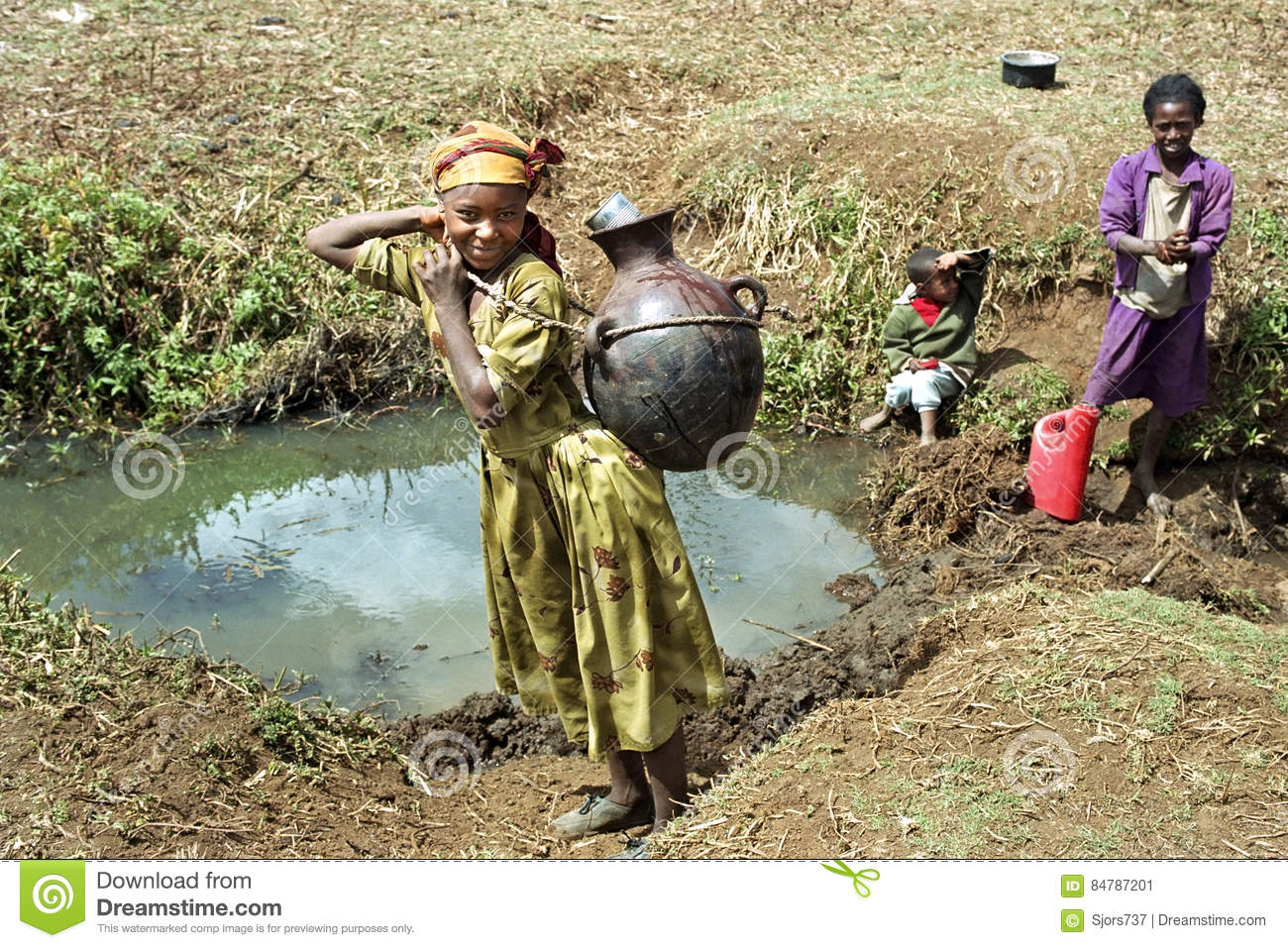Ethiopian Girls Fetching Water In Natural Water Well