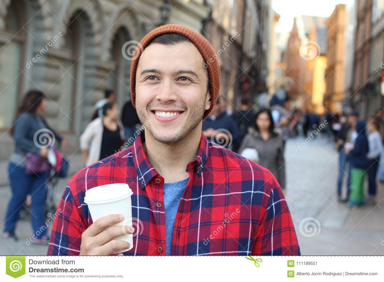 Ethnic male holding a disposable cup of coffee in the a crowded city street