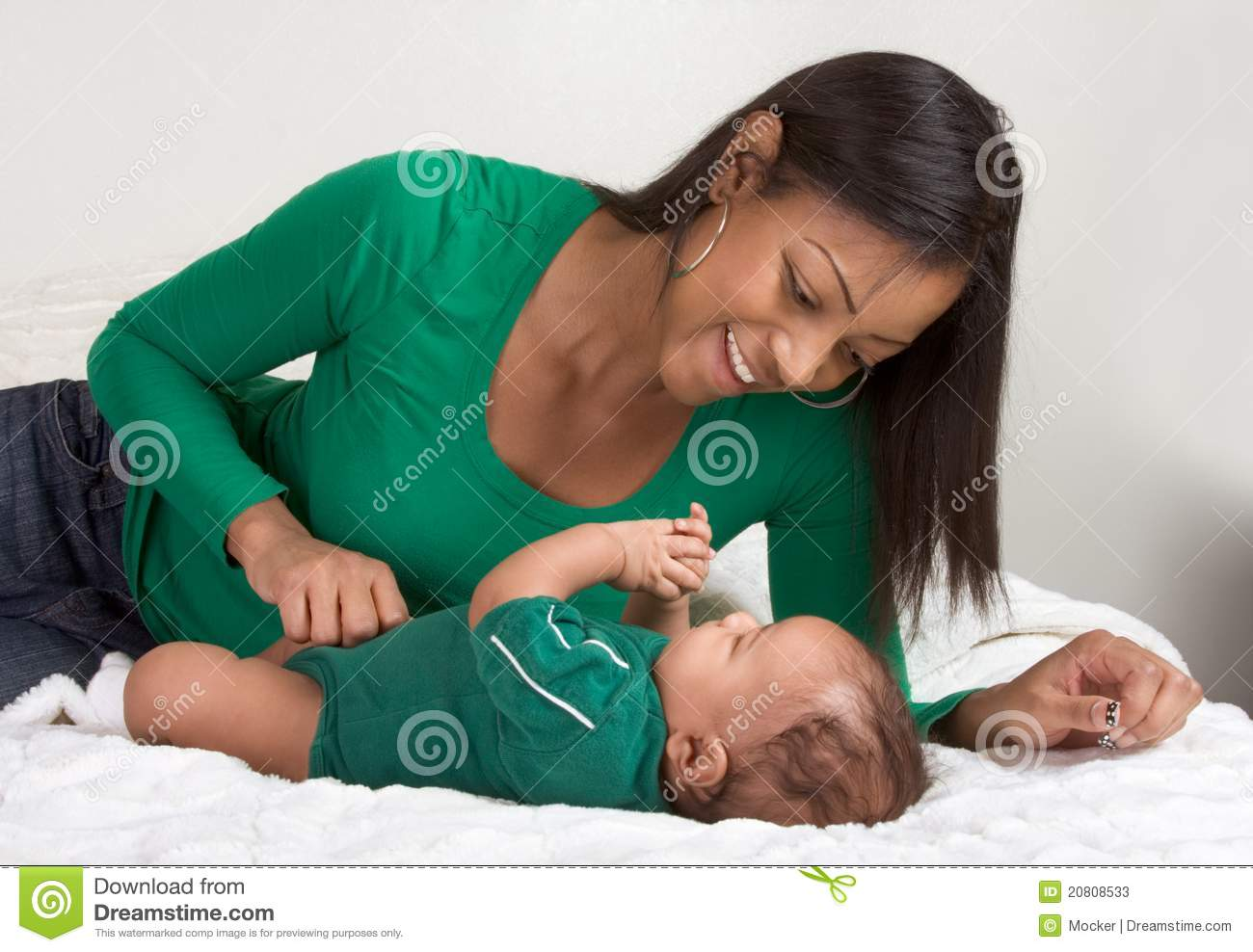 ethnic mother playing with her baby boy son on bed stock