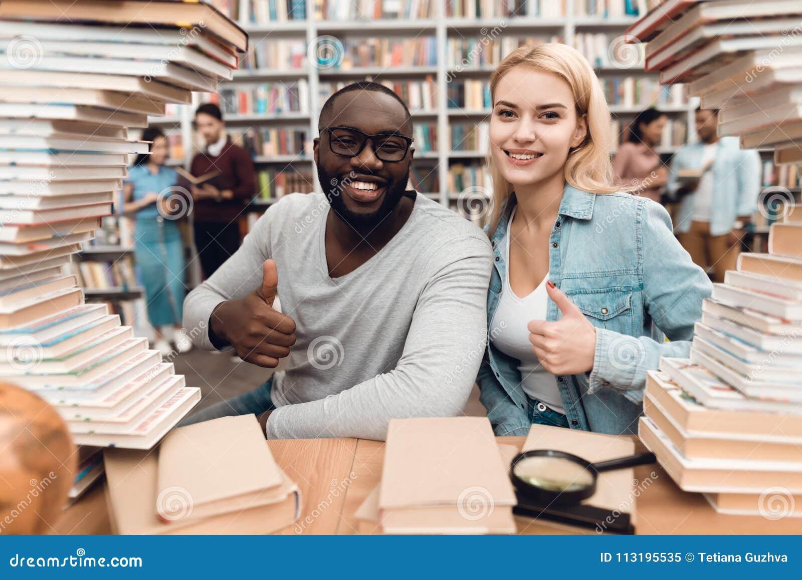 Ethnischer Afroamerikanerkerl und weißes Mädchen umgeben durch Bücher in der Bibliothek Studenten geben Daumen auf