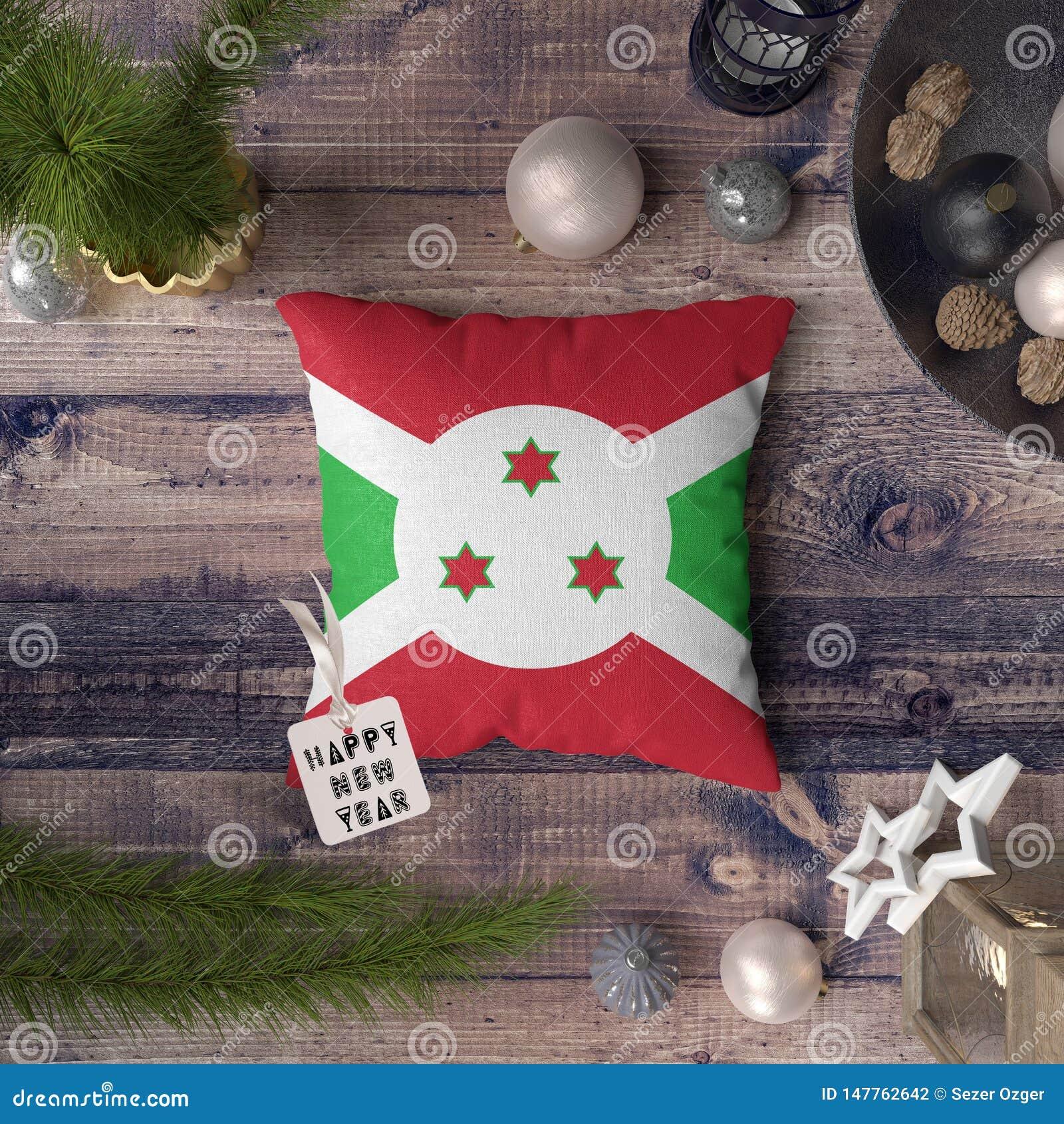 Etichetta del buon anno con la bandiera del Burundi sul cuscino Concetto della decorazione di Natale sulla tavola di legno con gl