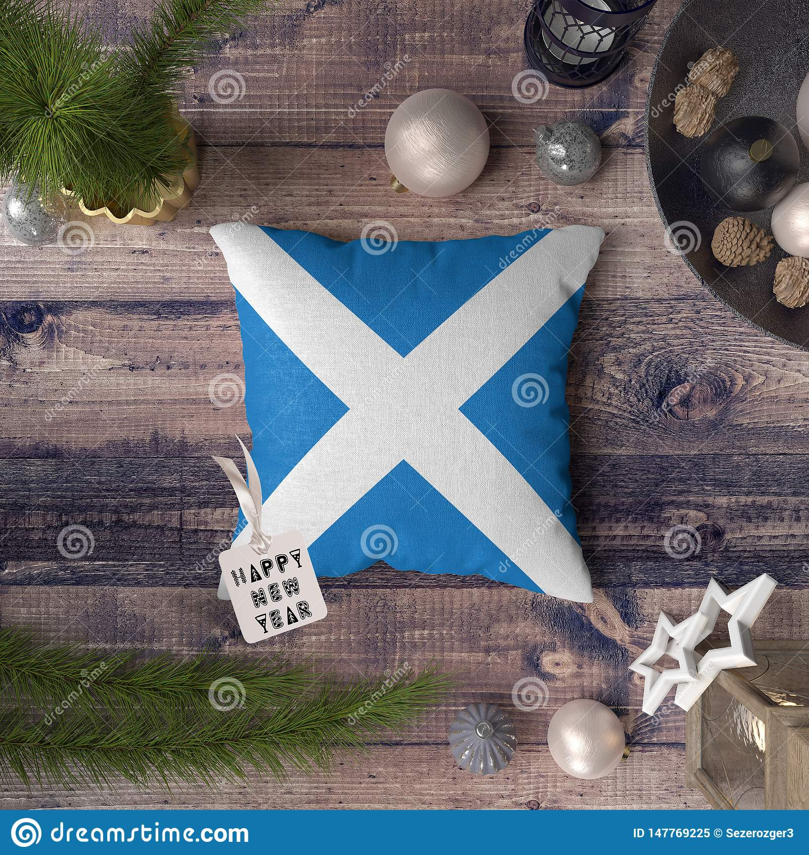 Etichetta del buon anno con la bandiera della Scozia sul cuscino Concetto della decorazione di Natale sulla tavola di legno con g