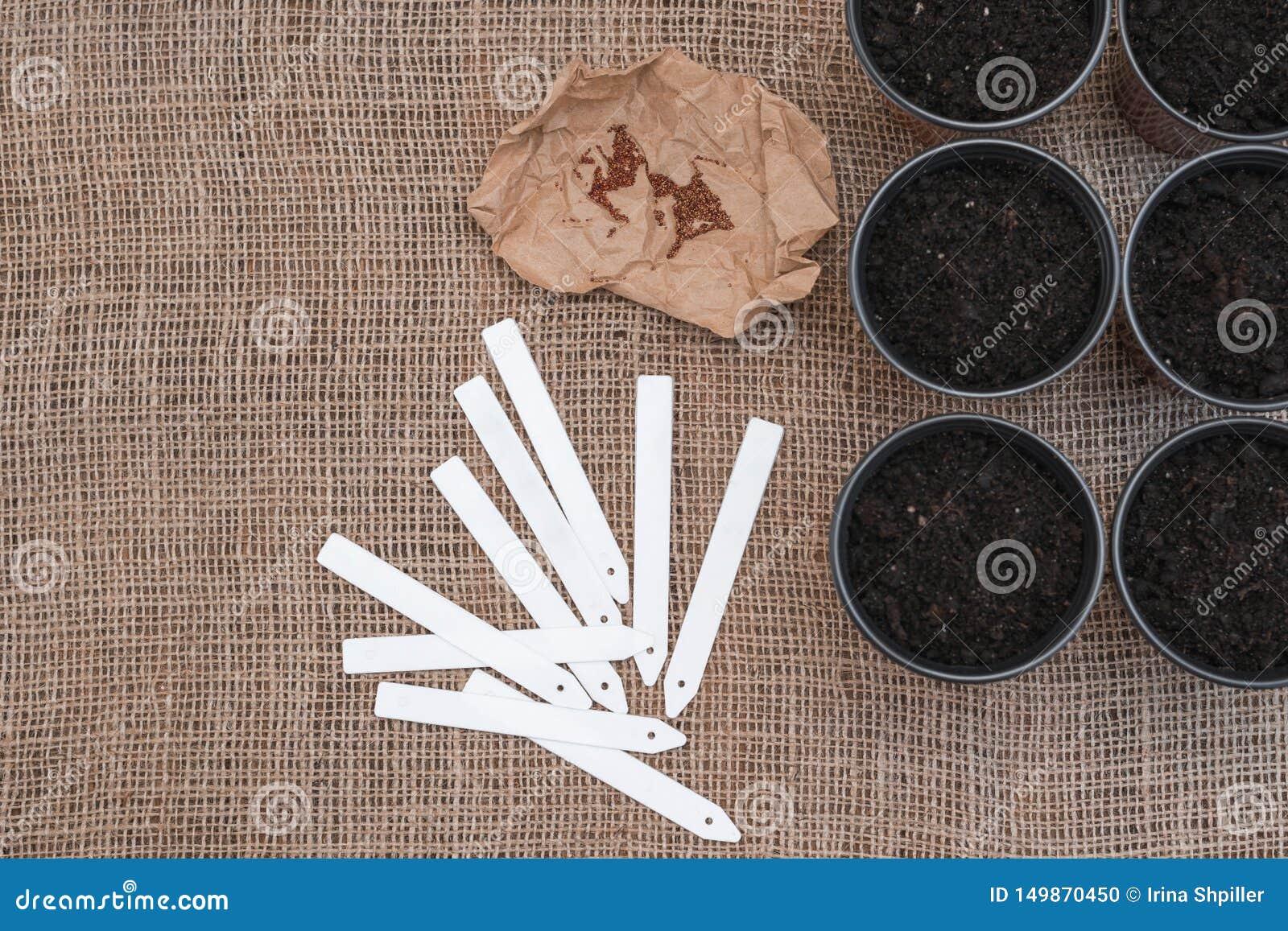 Etichette bianche e vasi marroni con suolo sul fondo della tela di sacco