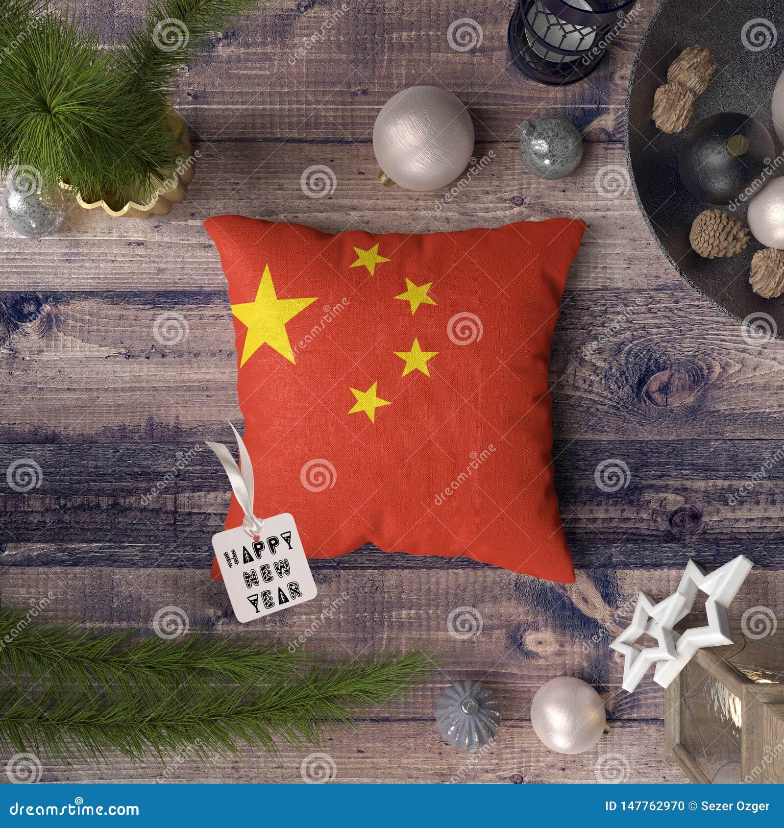 Etiqueta de la Feliz Año Nuevo con la bandera de China en la almohada Concepto de la decoraci?n de la Navidad en la tabla de made