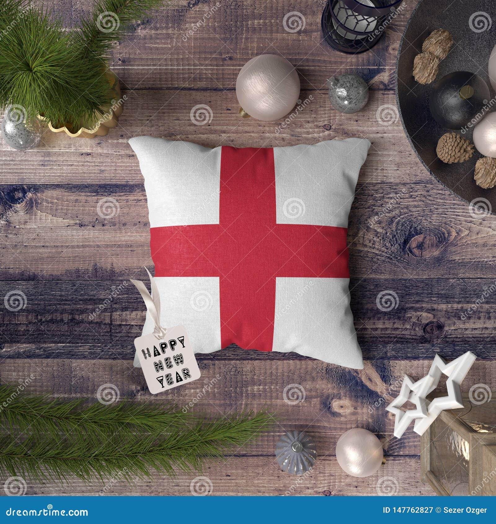 Etiqueta de la Feliz Año Nuevo con la bandera de Inglaterra en la almohada Concepto de la decoraci?n de la Navidad en la tabla de
