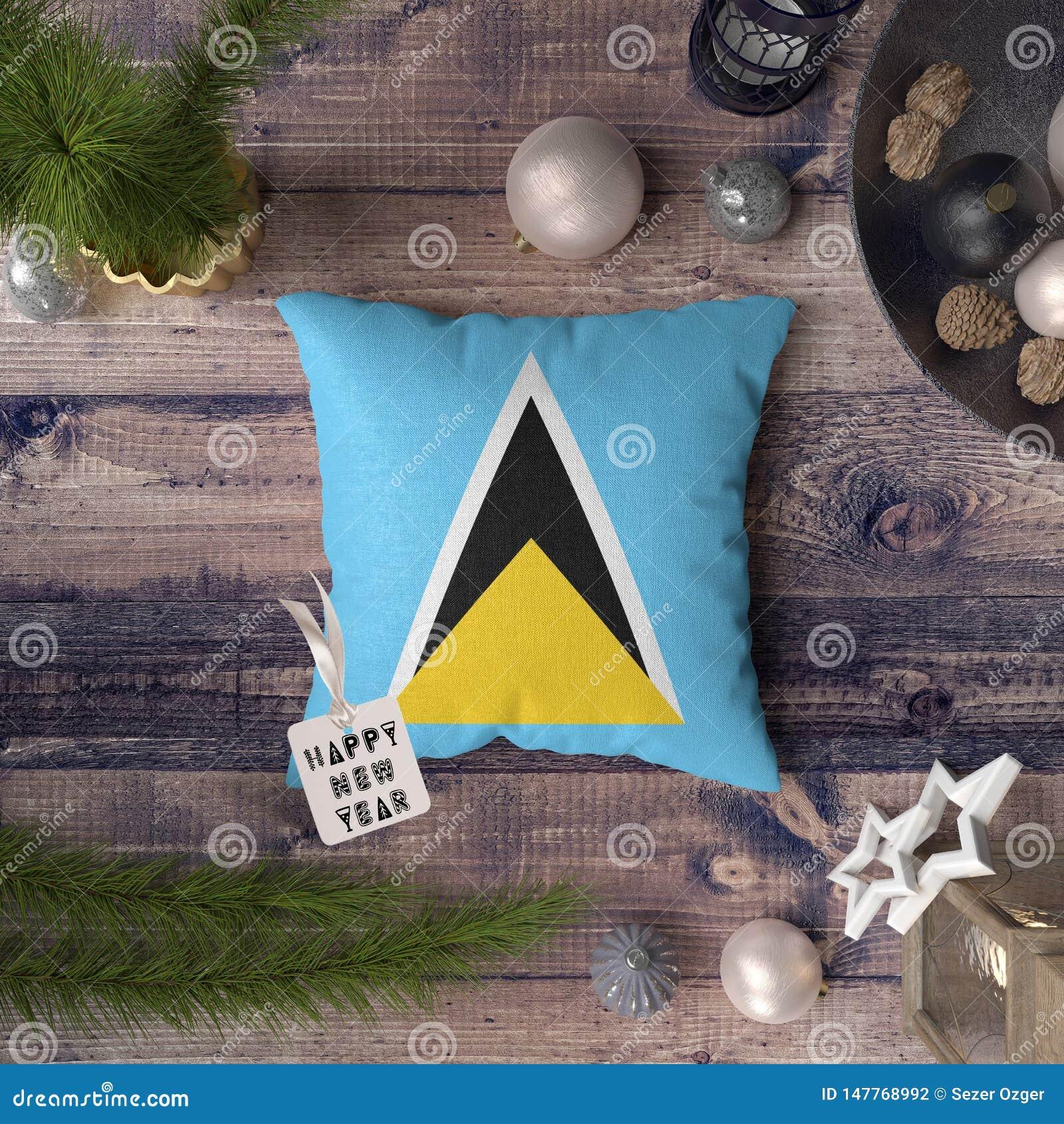 Etiqueta de la Feliz Año Nuevo con la bandera de la Santa Lucía en la almohada Concepto de la decoraci?n de la Navidad en la tabl