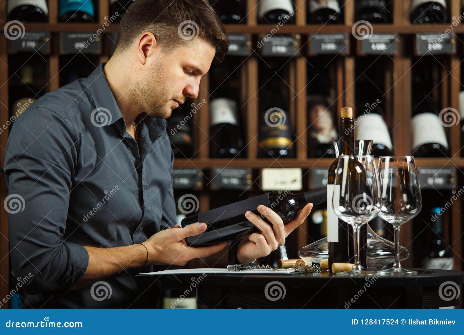Etiqueta de la lectura del Sommelier de la botella de vino en manos