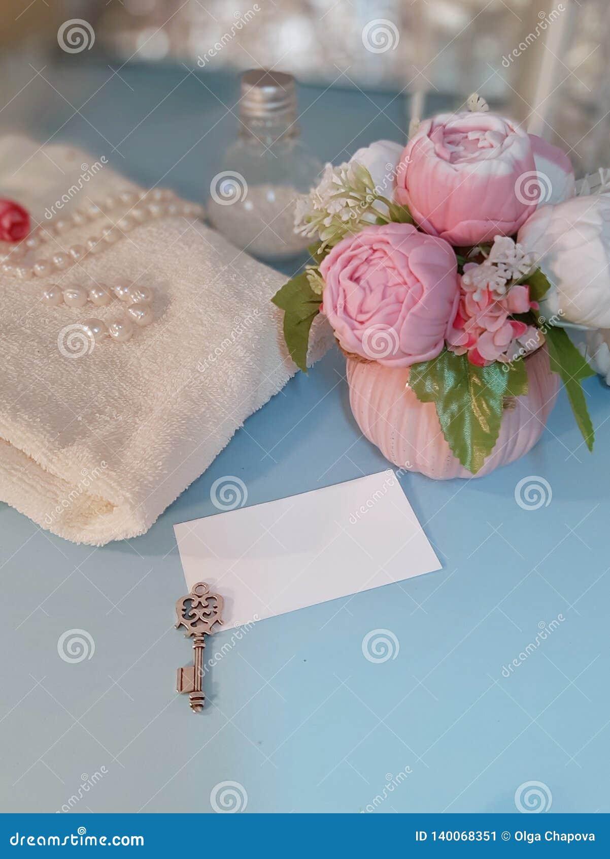 Etiqueta de papel vazia, chave de prata, ramalhete das flores e toalha no fundo azul
