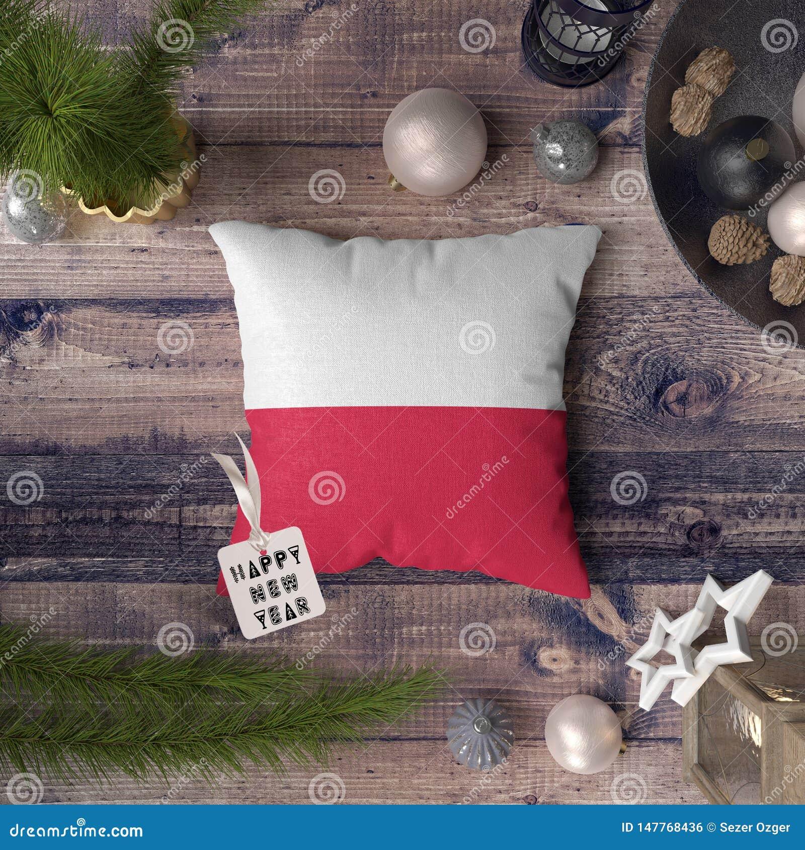 Etiqueta do ano novo feliz com a bandeira do Pol?nia no descanso Conceito da decora??o do Natal na tabela de madeira com objetos