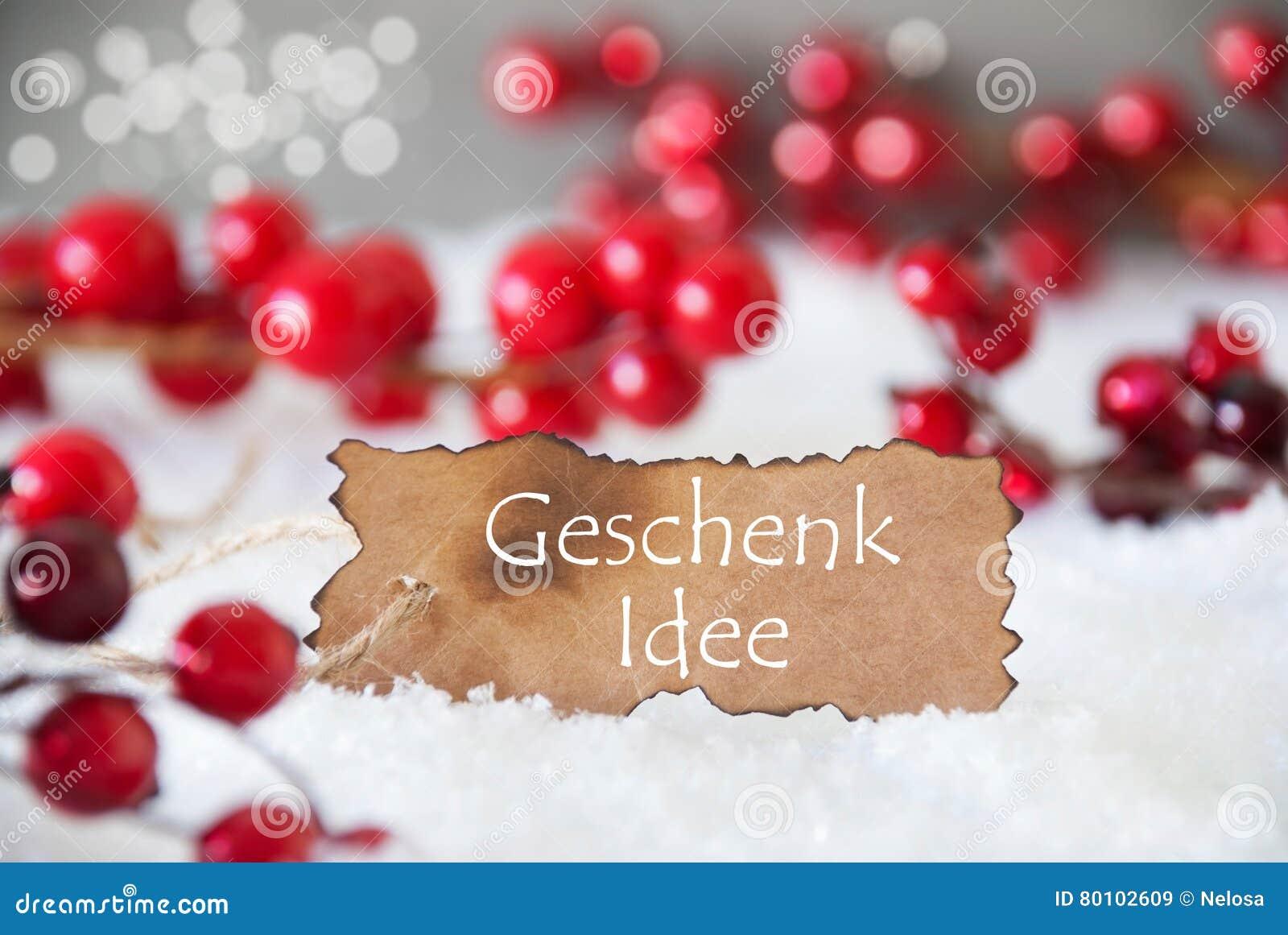 A etiqueta queimada, neve, Bokeh, texto Geschenk Idee significa a ideia do presente