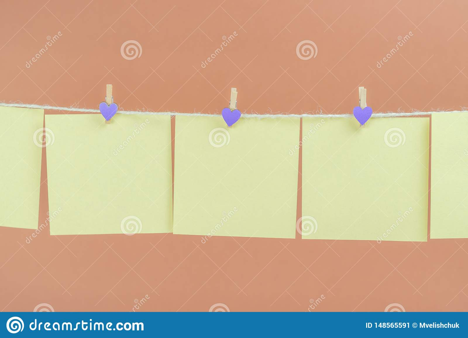 Etiquetas amarelas na corda com os pregadores de roupa isolados no fundo marrom