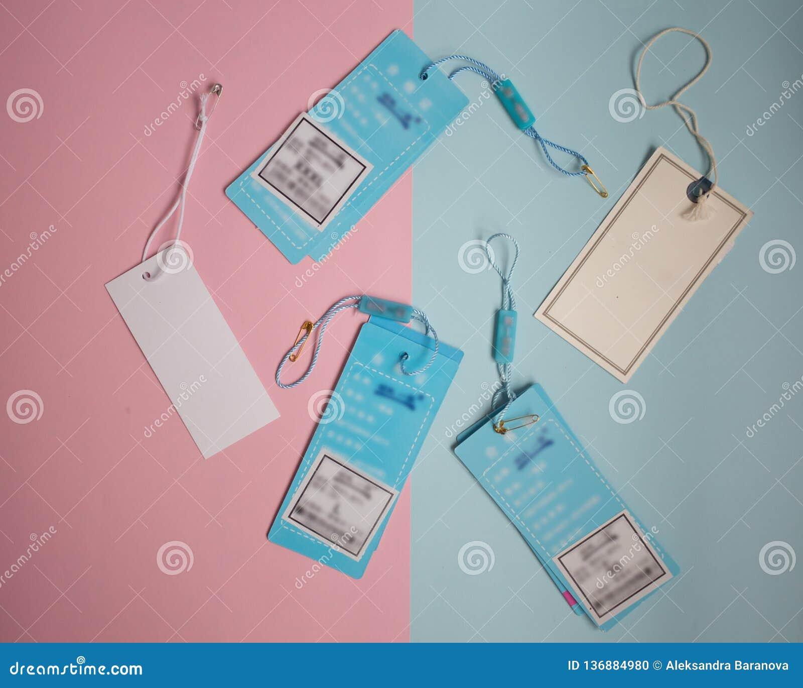 Etiquetas da roupa no rosa e no fundo azul