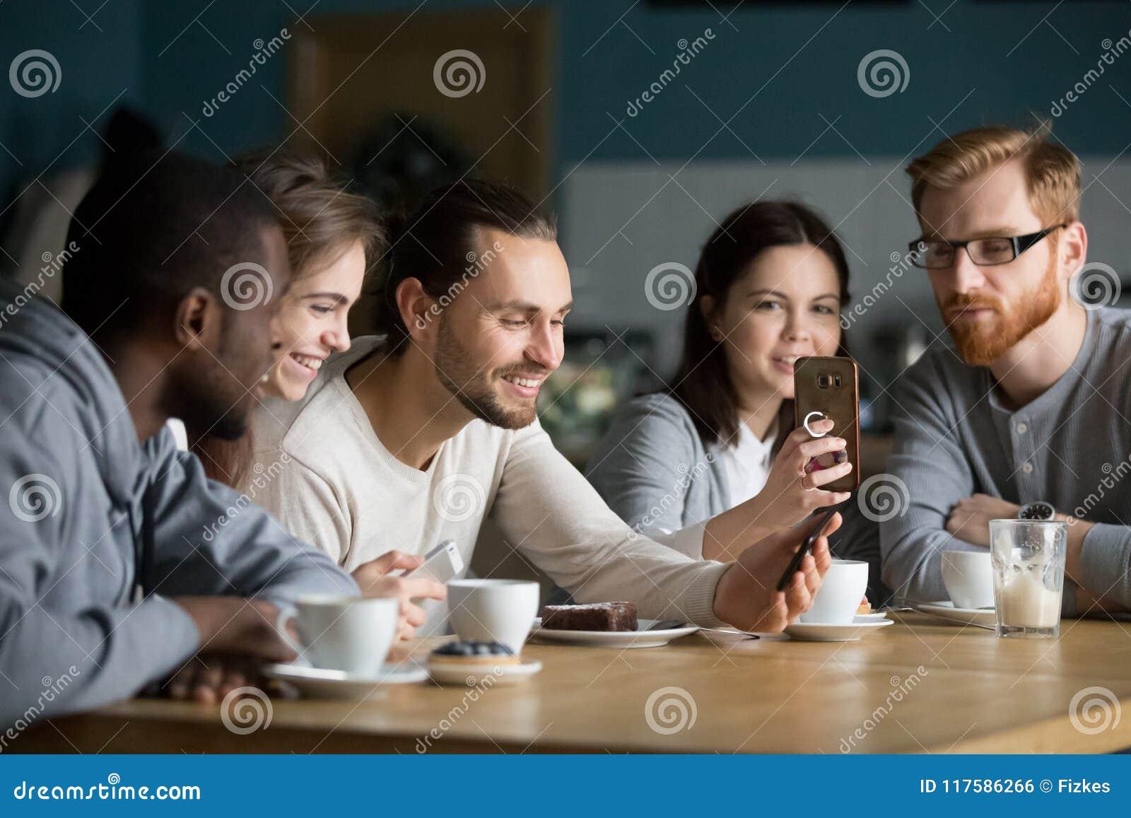 Etniczna grupa przyjaciele opowiada smartphones i używa przy m