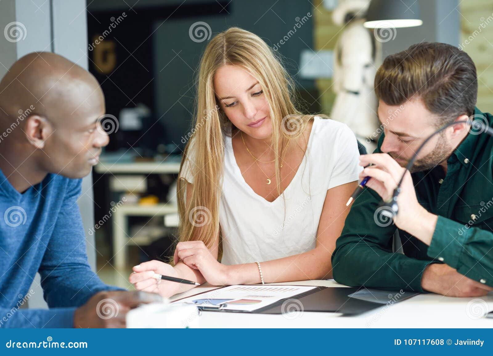 Etniczna grupa trzy młodzi ludzie studiuje wpólnie