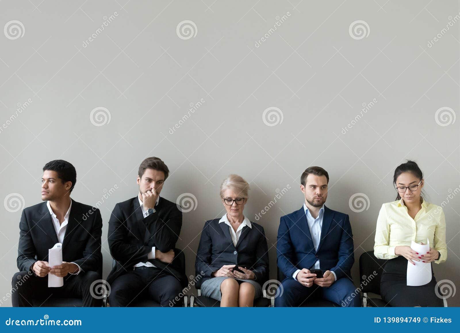 Etniczne wnioskodawcy siedzi w rząd kolejce wykładają narządzanie dla wywiadu
