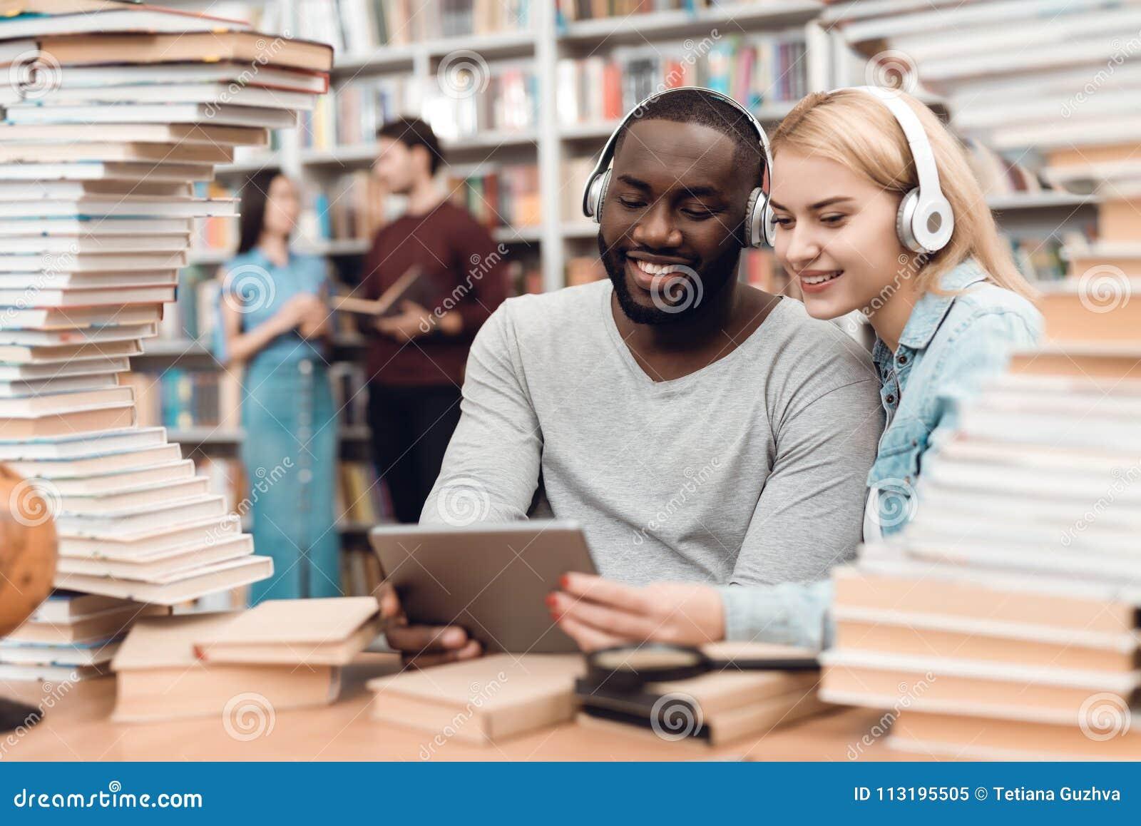 Etniczny amerykanina afrykańskiego pochodzenia facet i biała dziewczyna otaczający książkami w bibliotece Ucznie używają pastylkę
