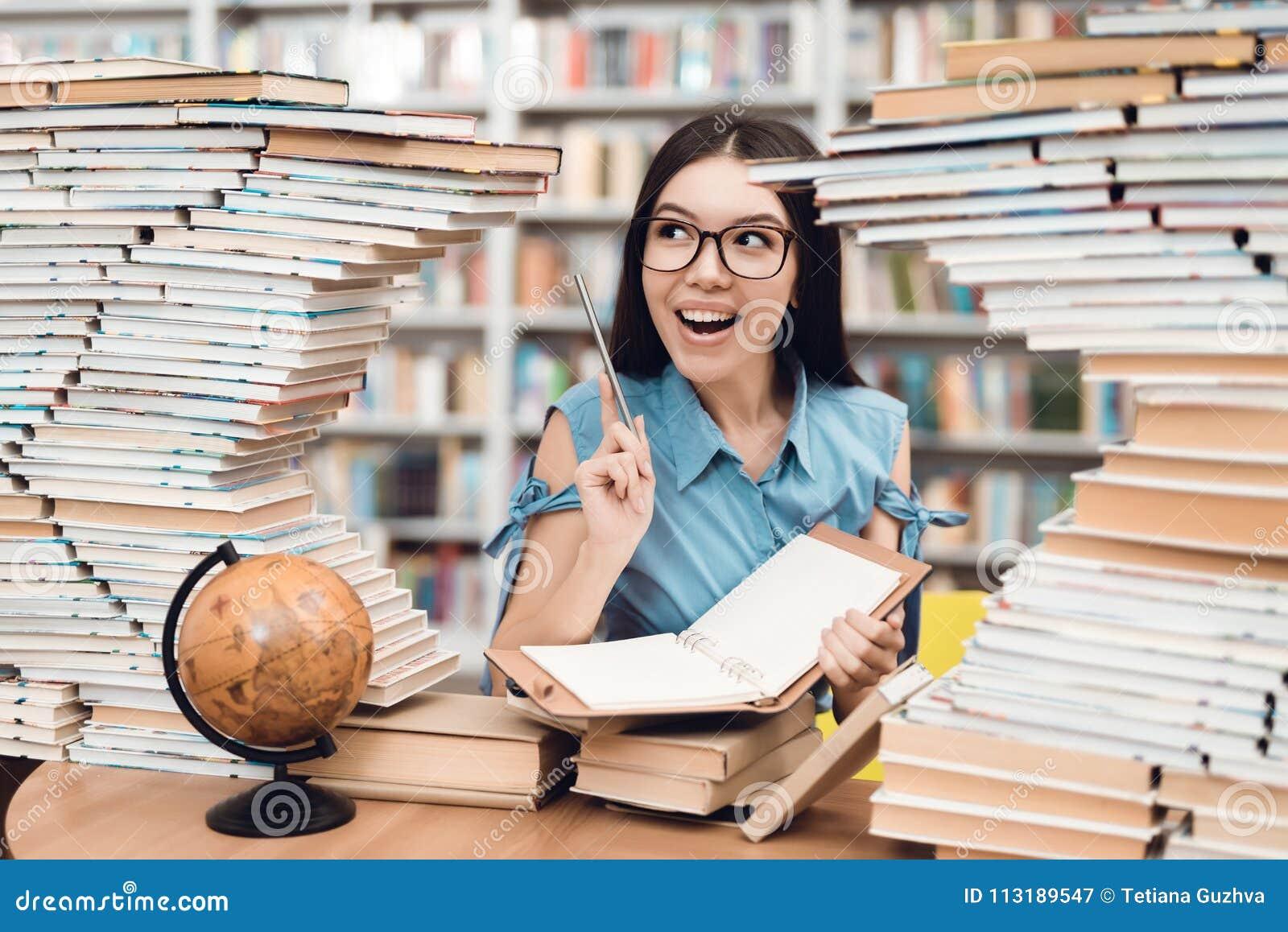 Etniczny azjatykci dziewczyny obsiadanie przy stołem otaczającym książkami w bibliotece Uczeń pisze w notatniku