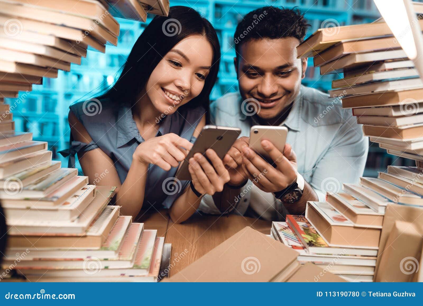 Etnisch Aziatisch meisje en Indische gemengde die raskerel door boeken in bibliotheek wordt omringd De studenten gebruiken telefo