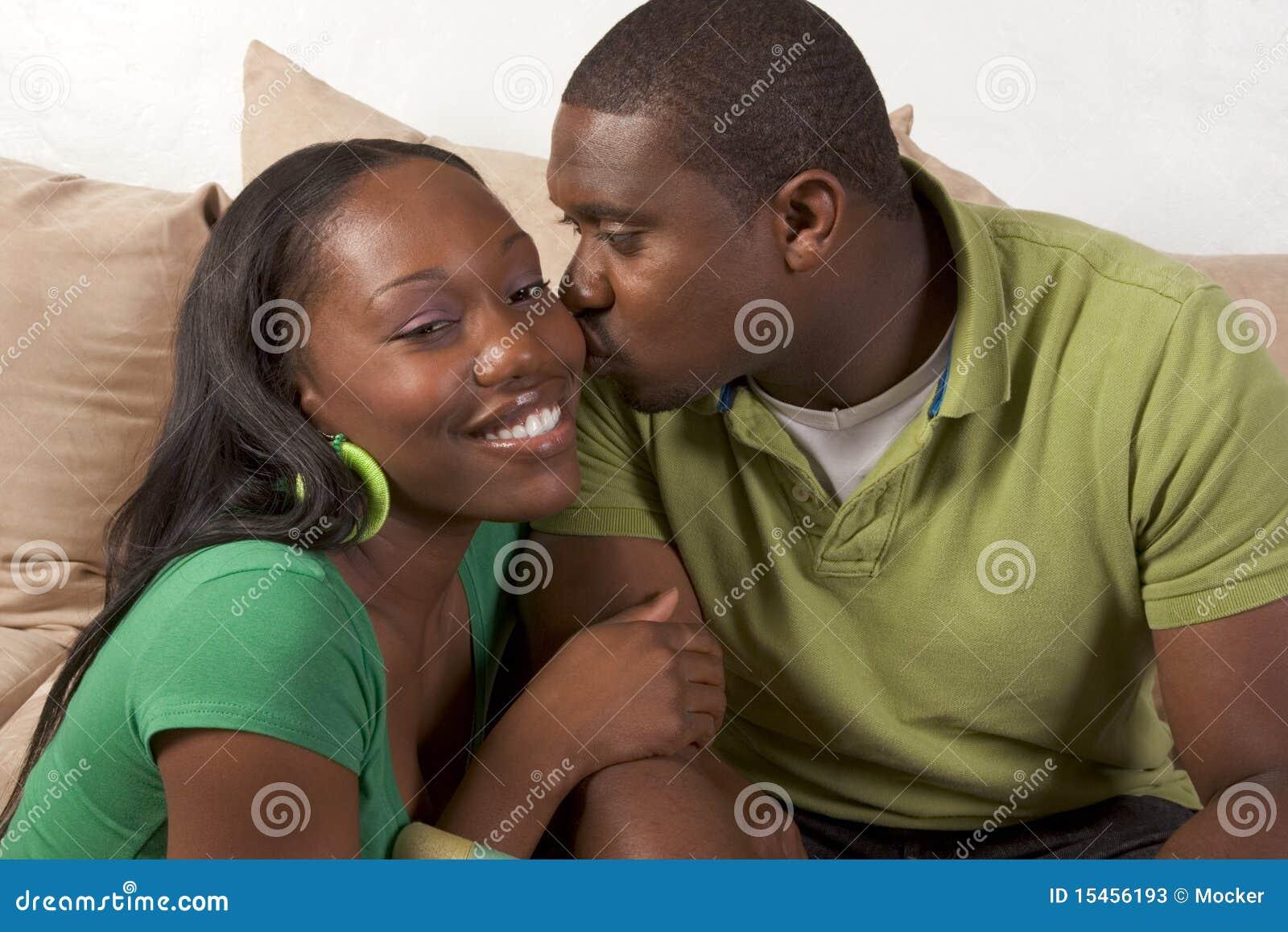 Etniskt lyckligt sittande barn för svarta soffapar