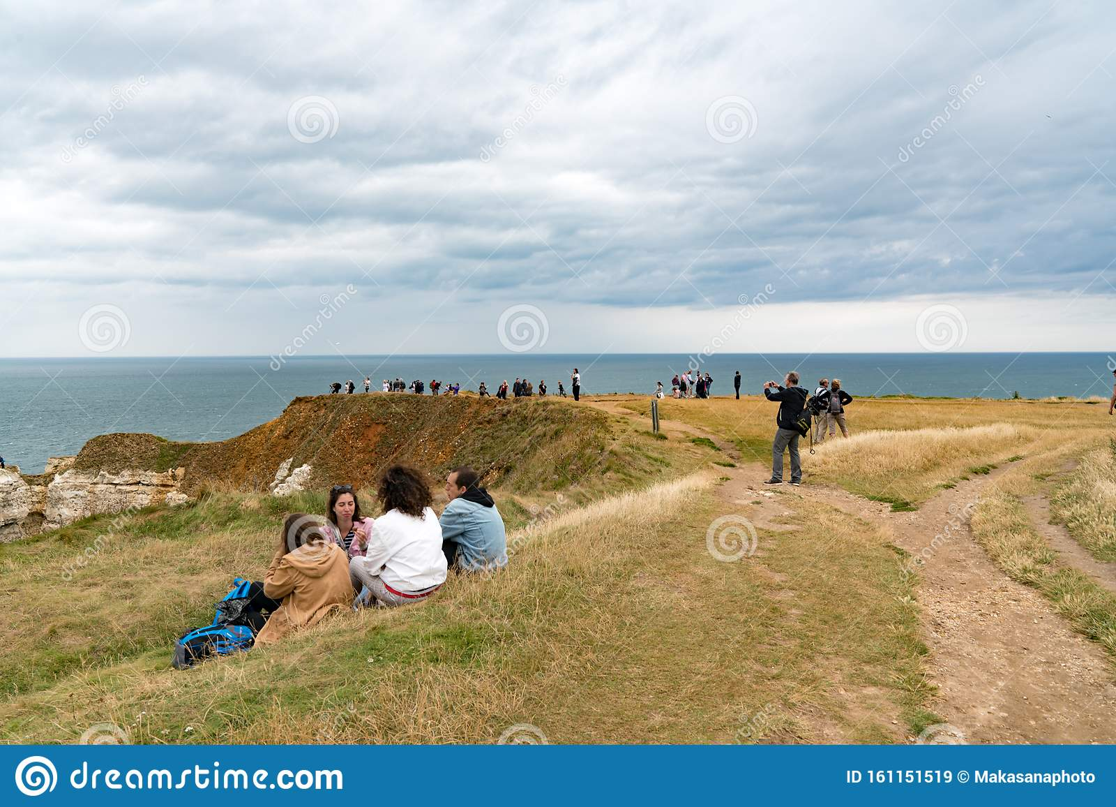 Tourists Enjoy Hiking And Picknicking On The Normandy Coast Along