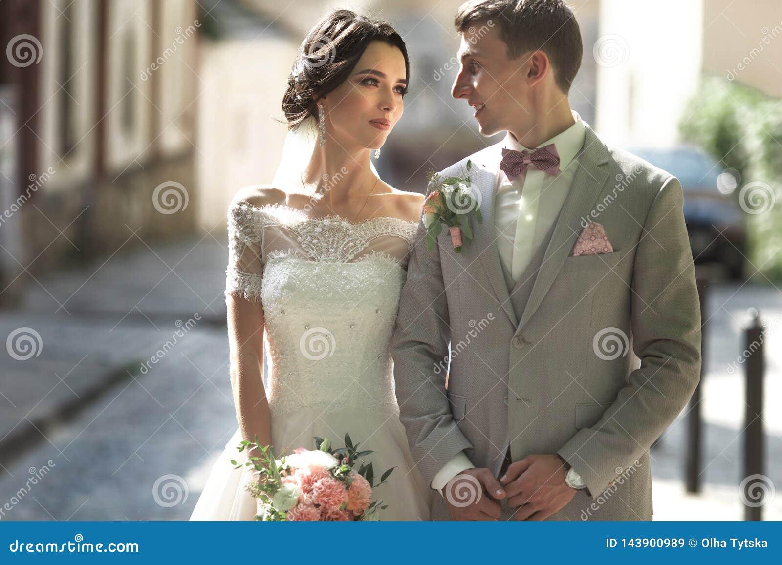 Ett älska par av nygifta personer går i staden och leende Bruden i en härlig klänning, brudgummen klädde stylishly