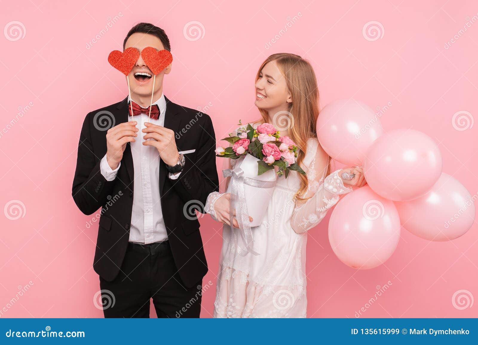 Ett älska par, en man som rymmer två pappers- hjärtor i hans ögon och en kvinna som rymmer en bukett av blommor, på en rosa bakgr