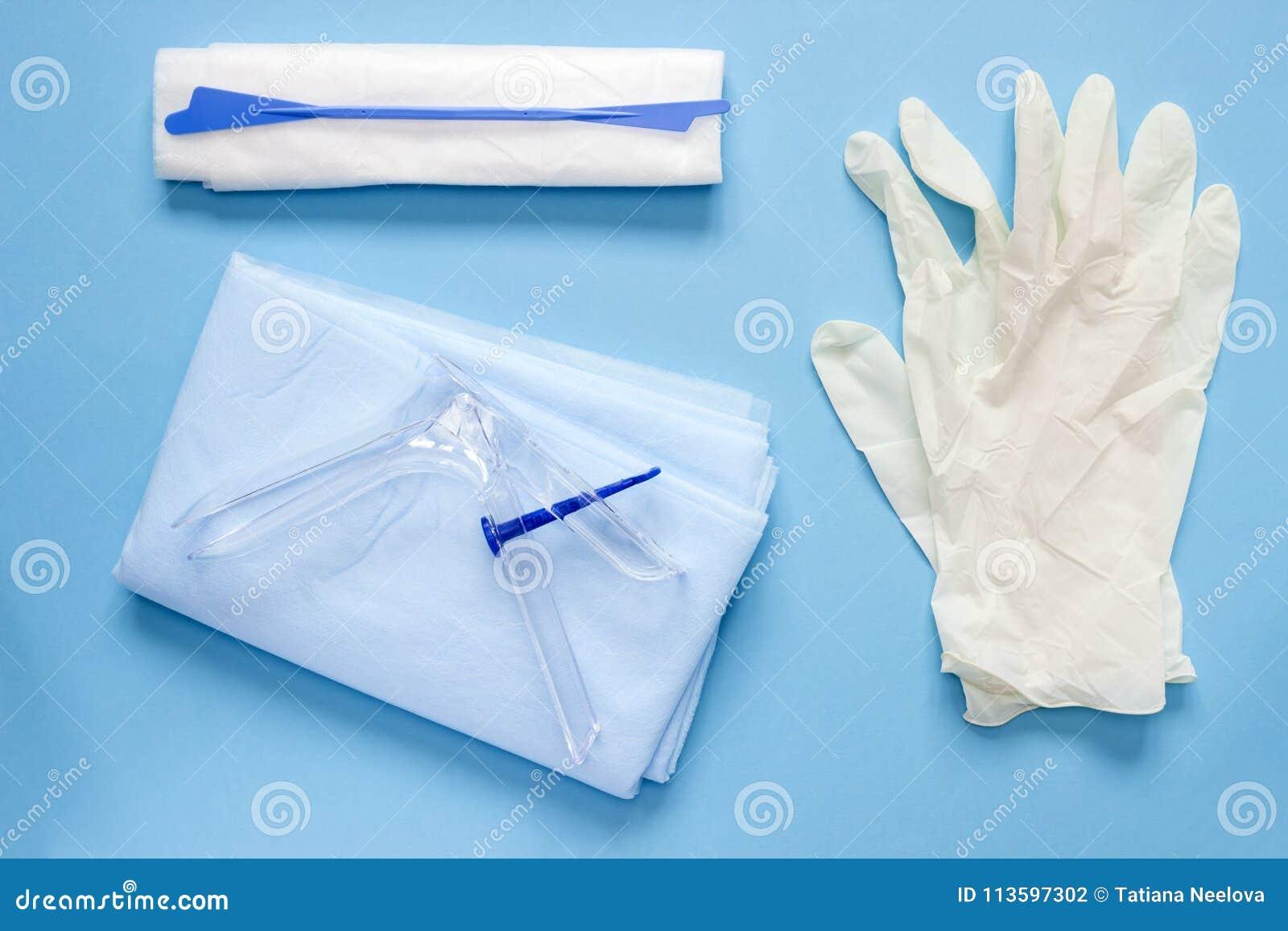 Ett över huvudet foto av den vaginal speculumen, servetten, medicinhandskarna och spateln De medicinska hjälpmedlen för att rymma