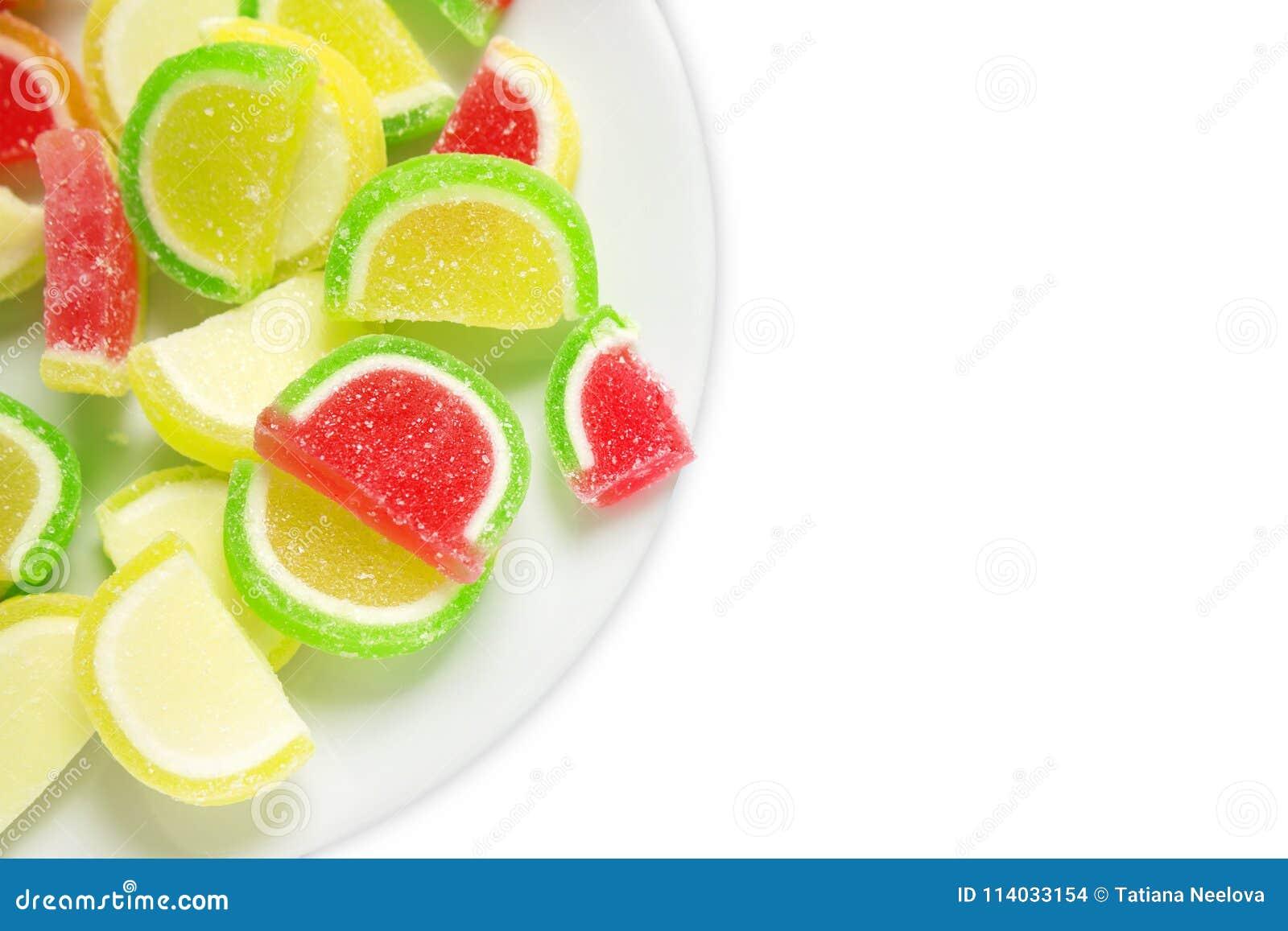 Ett över huvudet foto av söt smaklig söt färgrik gelémarmelad Vibrerande blandade godisar eller sötsaker som isoleras på vit bakg