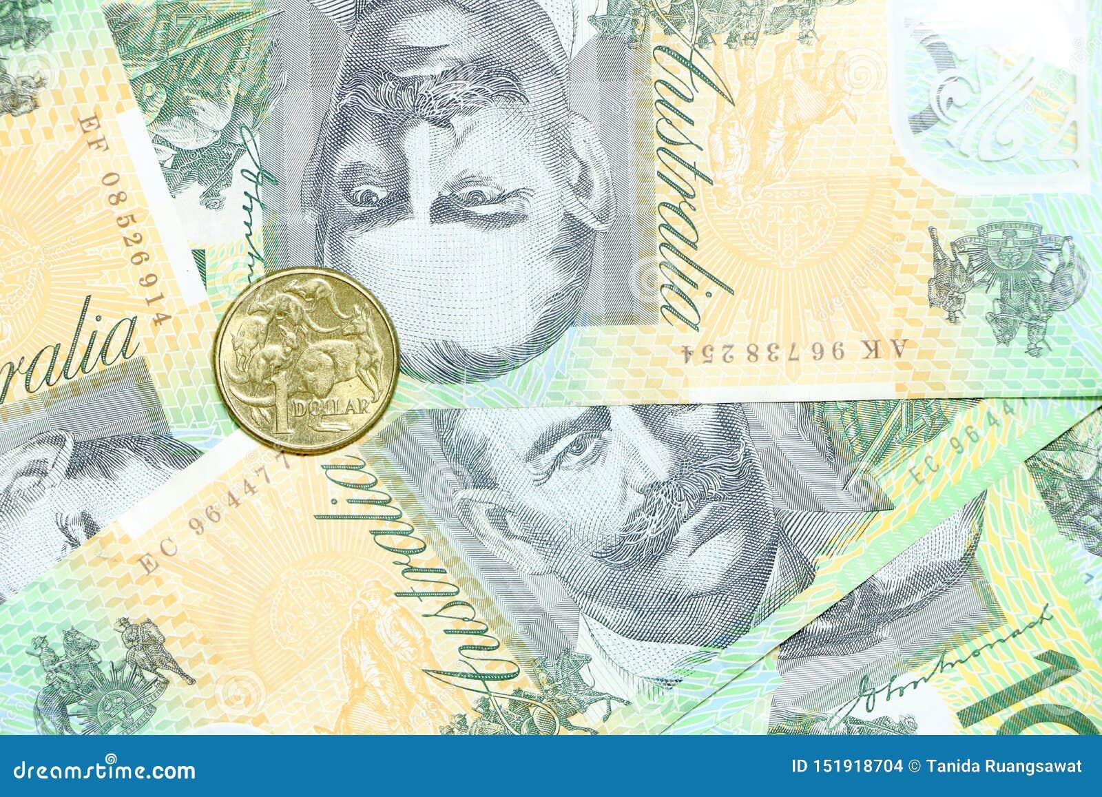 Ett aud-dollarmynt på gruppen av 100 australiska anmärkningar för dollar traver bakgrund