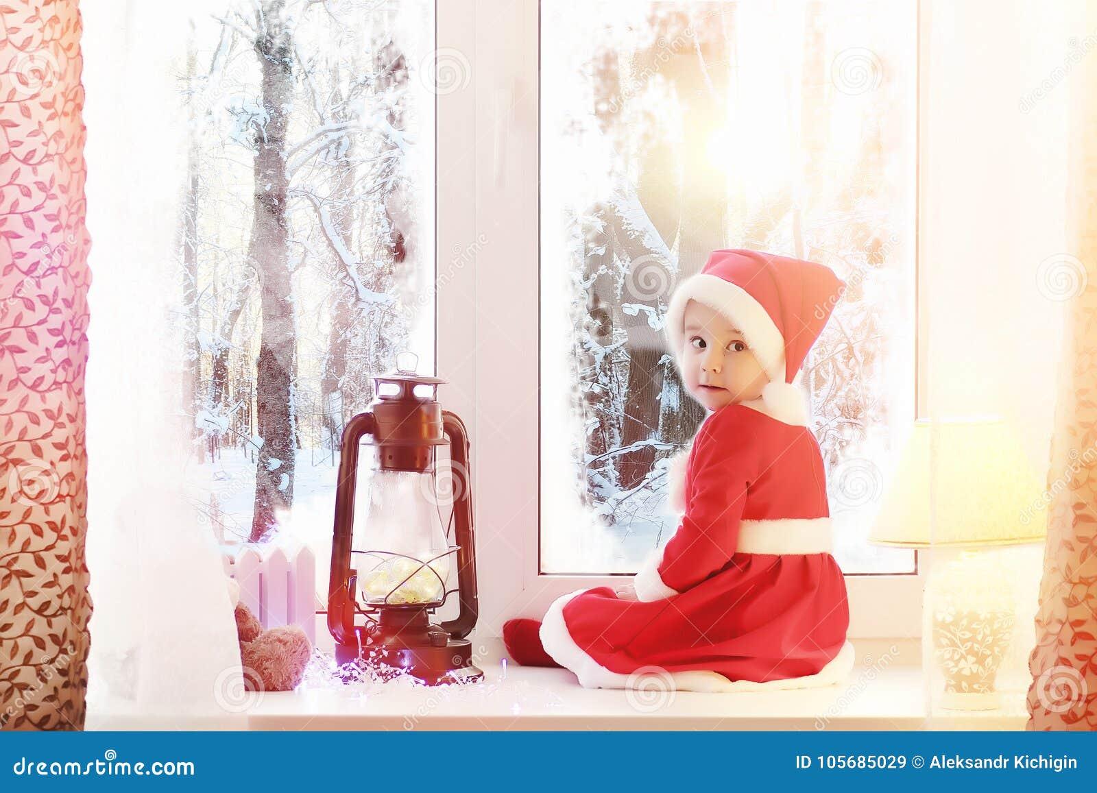 Ett barn i det nya året ser ut fönstret Barn är waitien