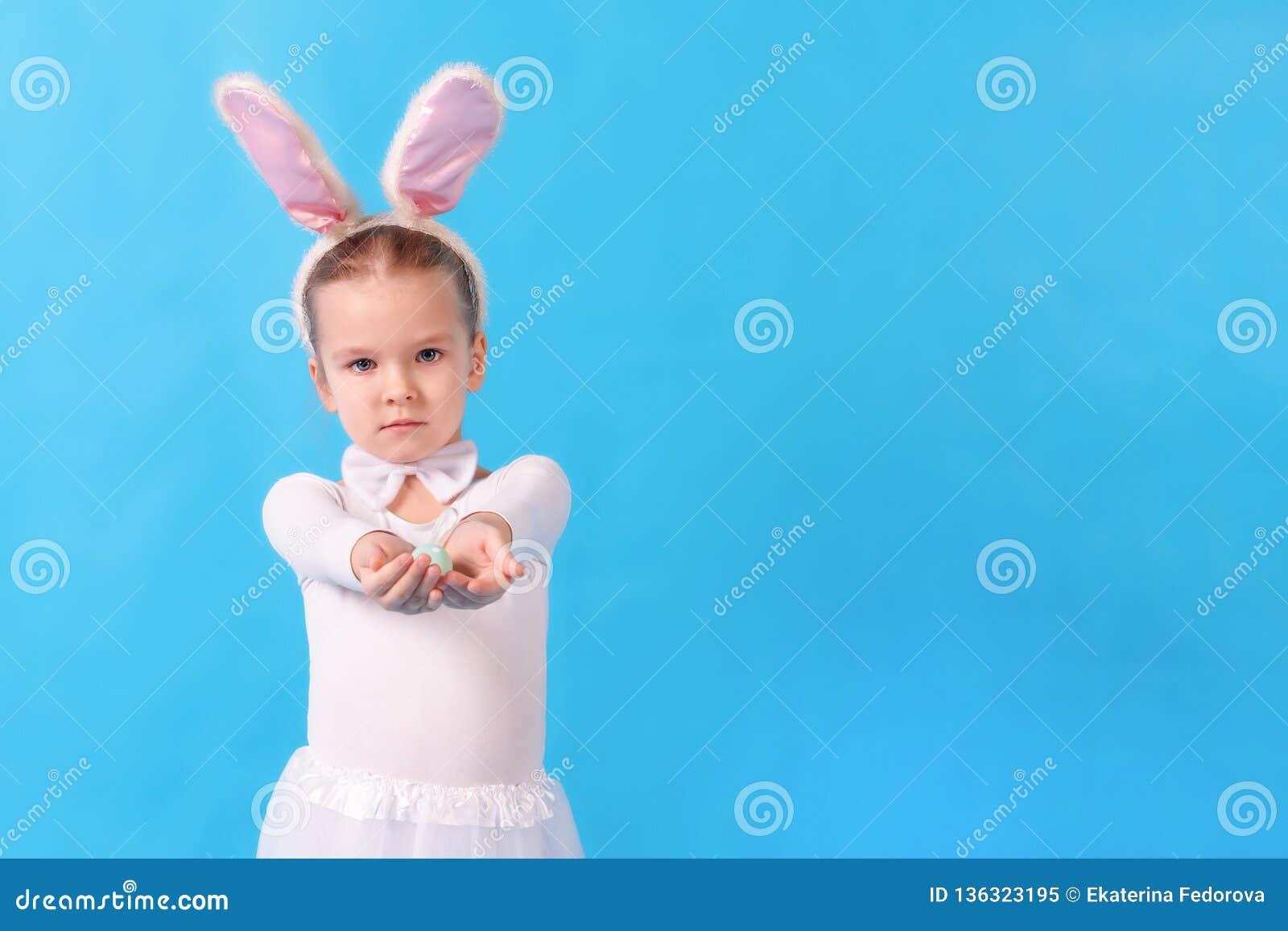 Ett barn som bär en vit kanin Lite sträcker flickan ett påskägg i hennes händer Gullig kanin, feriesymbol brigham