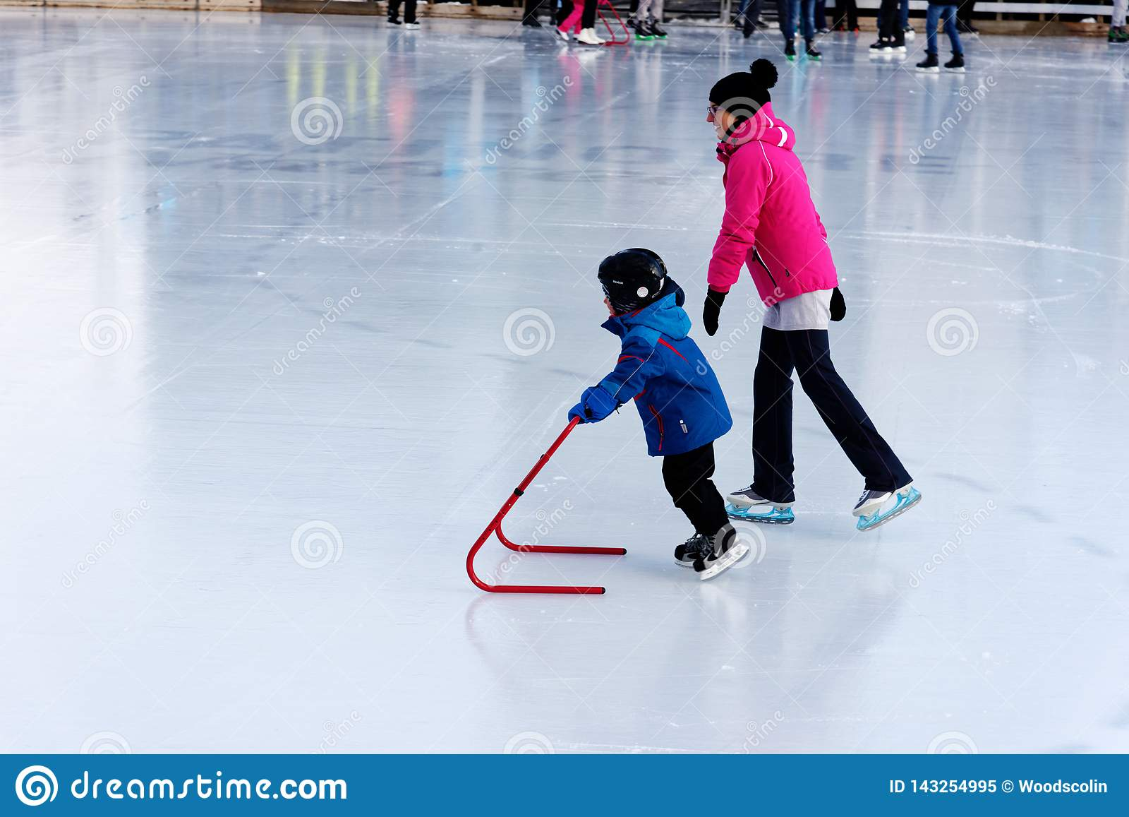 Ett barn som lär att åka skridskor på en utomhus- isbana i Montreal