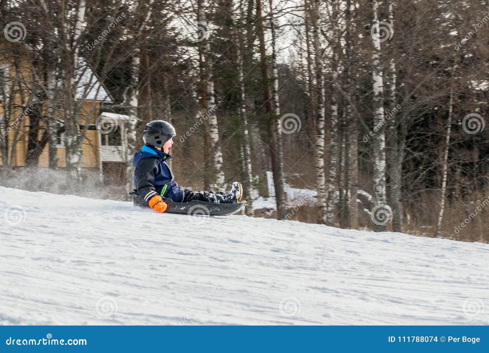 Ett barn som rider en sluttande pulka, profilsikt