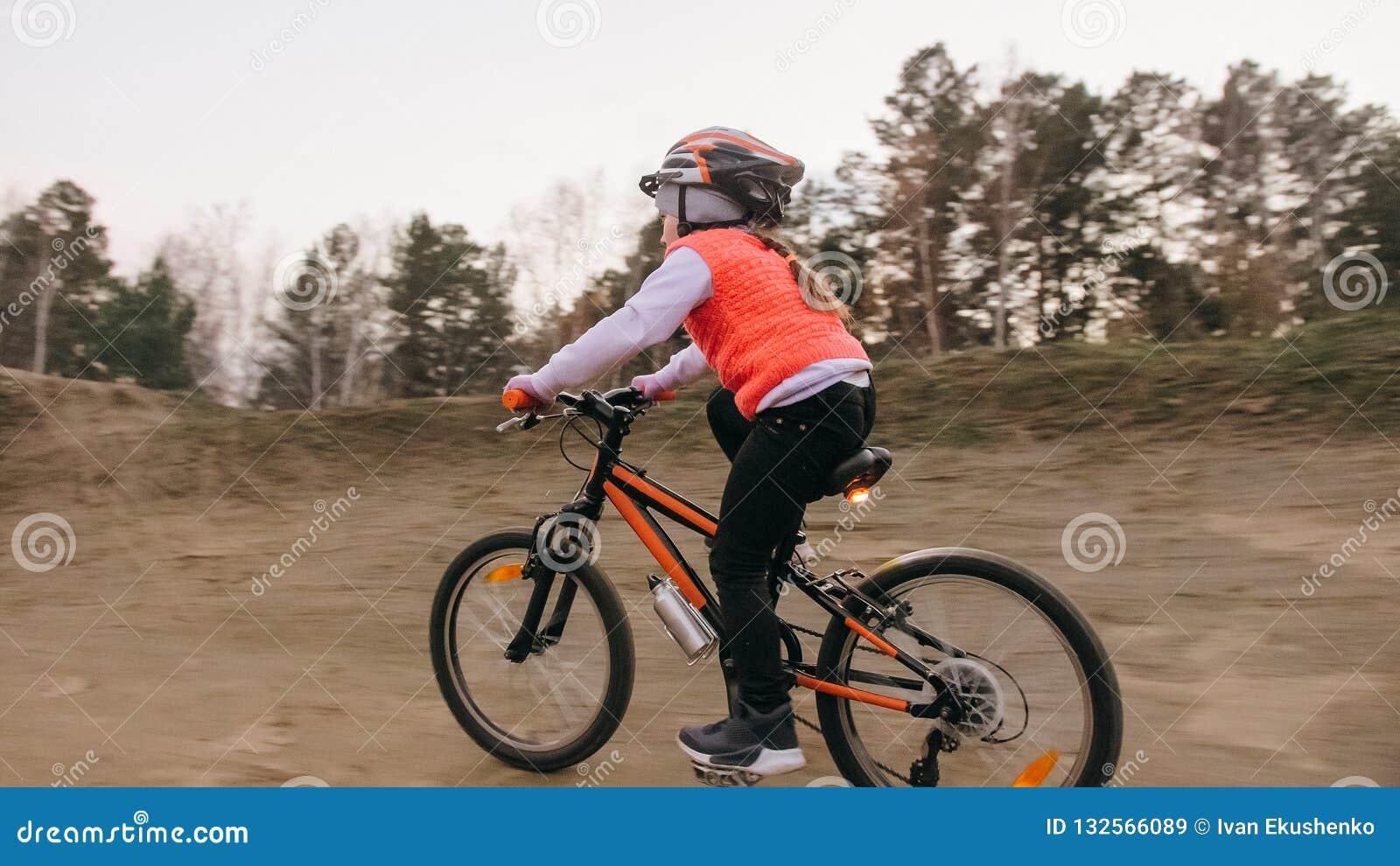 Ett caucasian spår för väg för barnrittcykel i smuts parkerar Orange cirkulering för flickaridningsvart i löparbana Ungen går att