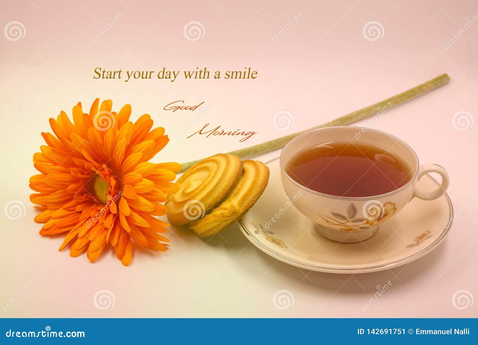 Ett citationsteckenfoto för bra morgon med kopp te, blomman och kakor