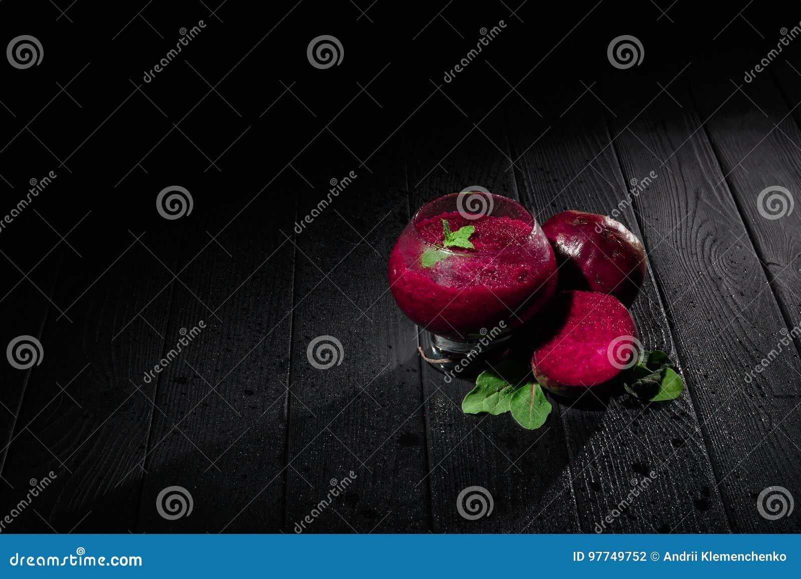 Ett efterrättexponeringsglas med vin-färgad tunn välling på en svart bakgrund Sund smoothie med rödbeta, mintkaramellen och socke