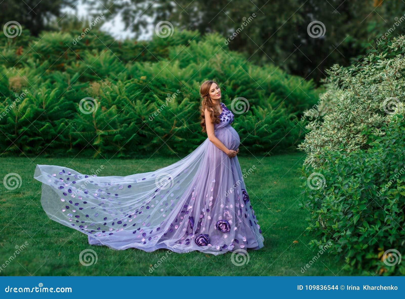 Ett elegant, gravid kvinna går i en härlig trädgård i en lyxig blom- lila klär med ett långt drev kronärtskockan