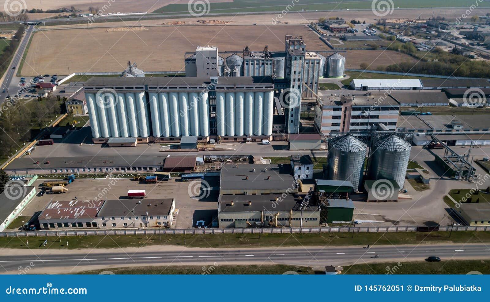 Ett enormt oljeraffinaderi med metallstrukturer, r?r och destillation av komplexet med brinnande ljus p? skymning flyg- sikt