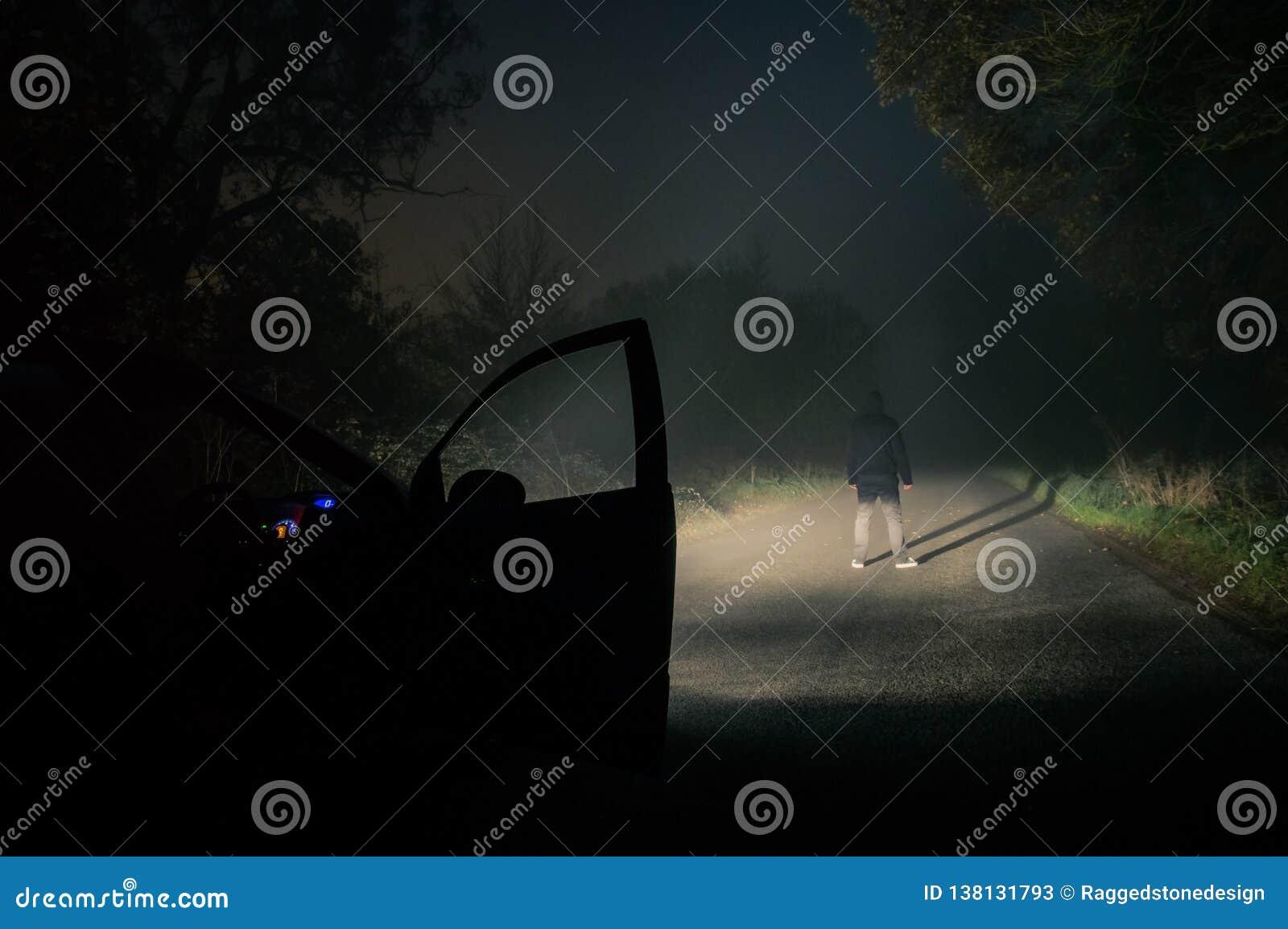 Ett ensamt med huva diagram anseende på en tom dimmig spöklik väg på natten Markerat med bilbillyktor