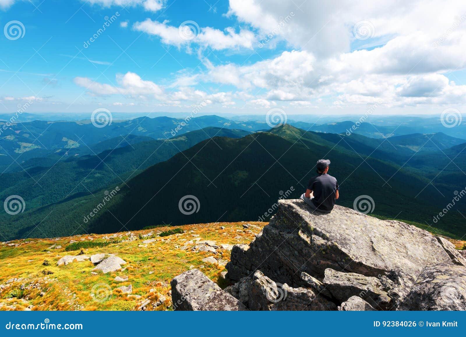 Ett ensamt turist- sammanträde på kanten av klippan