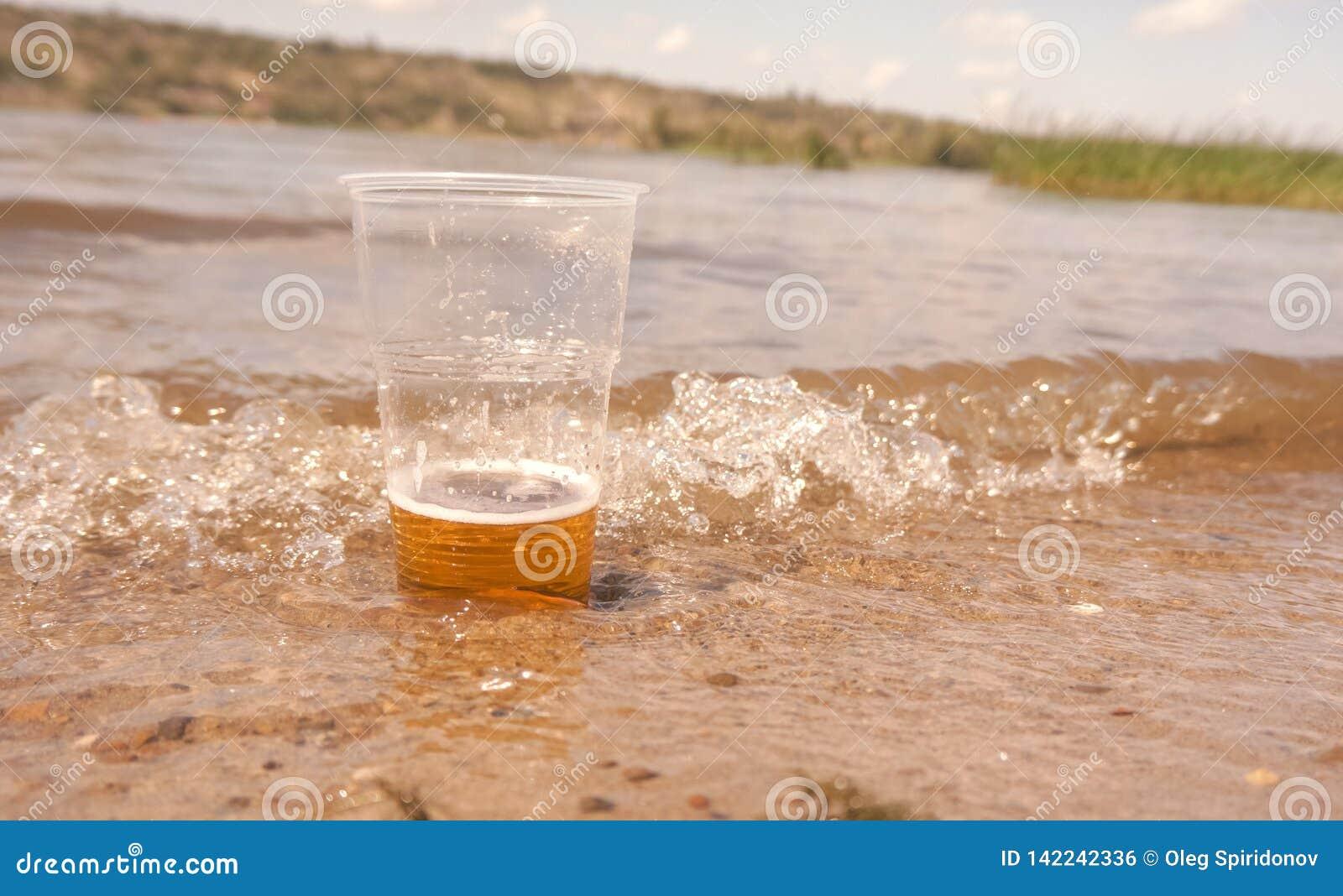 Ett exponeringsglas av öl i vattnet