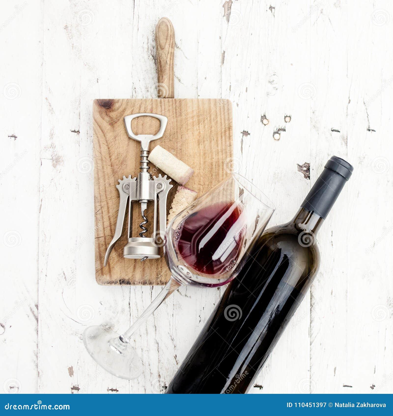Ett exponeringsglas av rött vin-, flask-, korkskruv- och vinkorkar på rusti